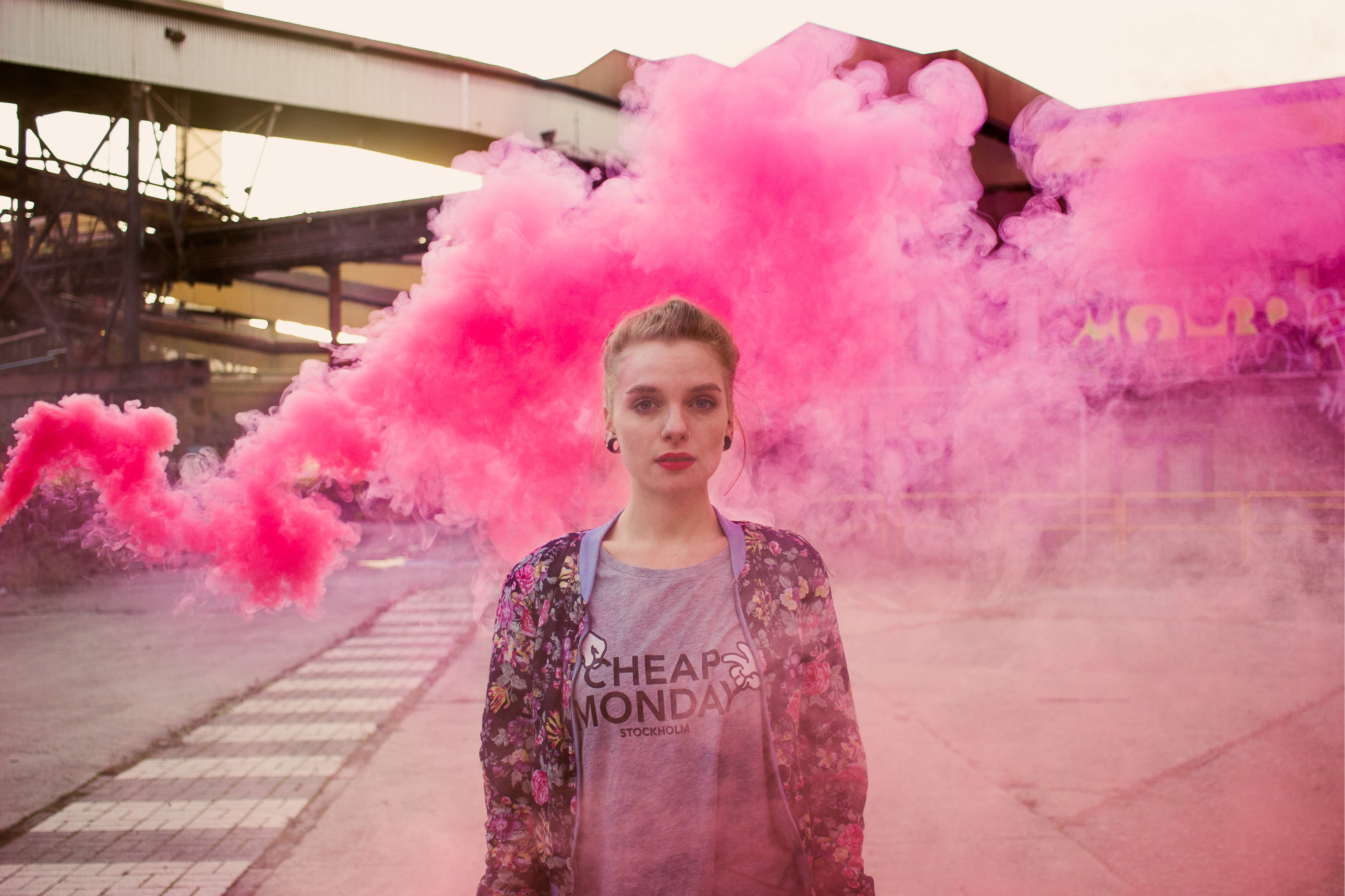Young woman looks pensive in front of a cloud of pink smoke