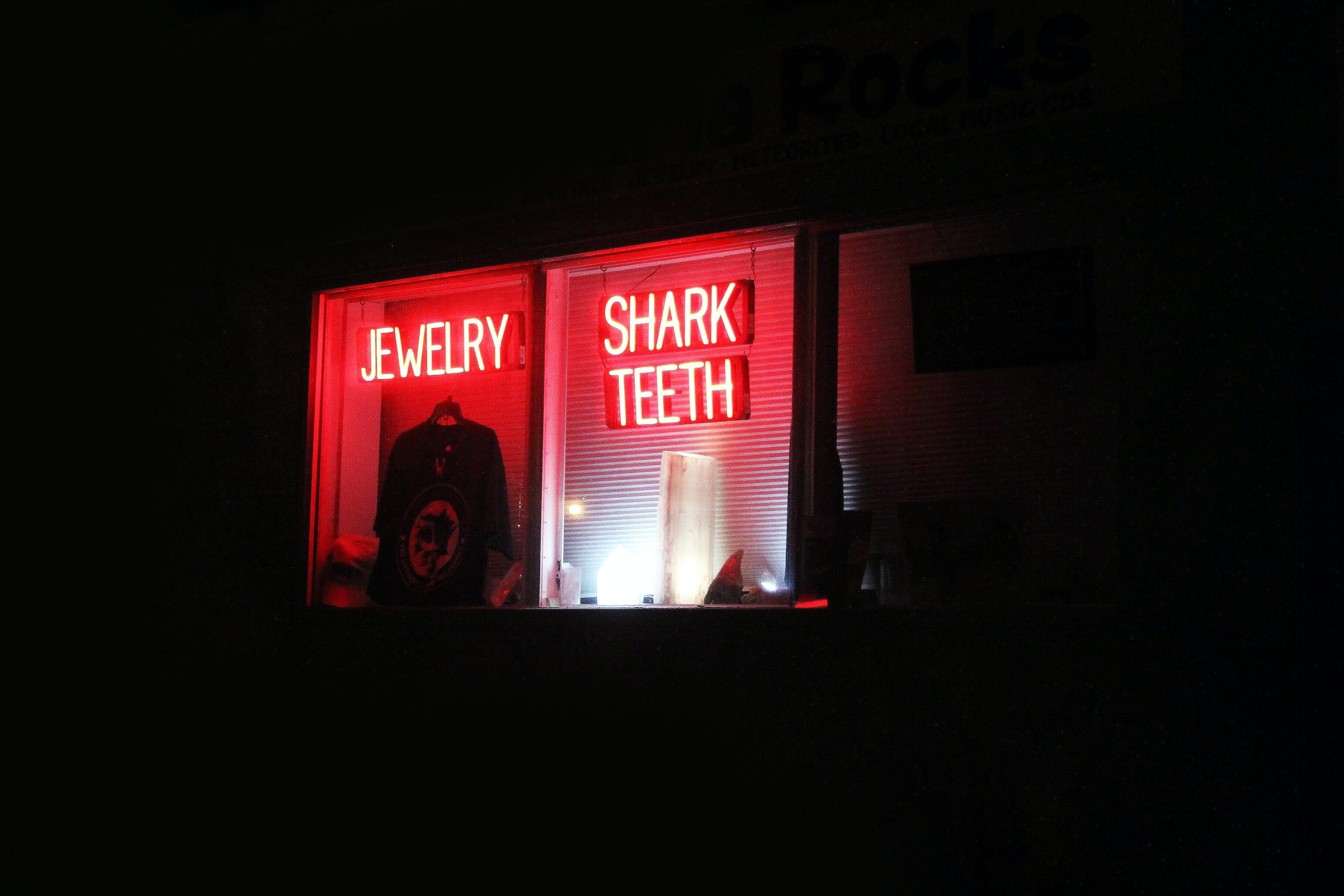 Shark Teeth neon signage on glass window