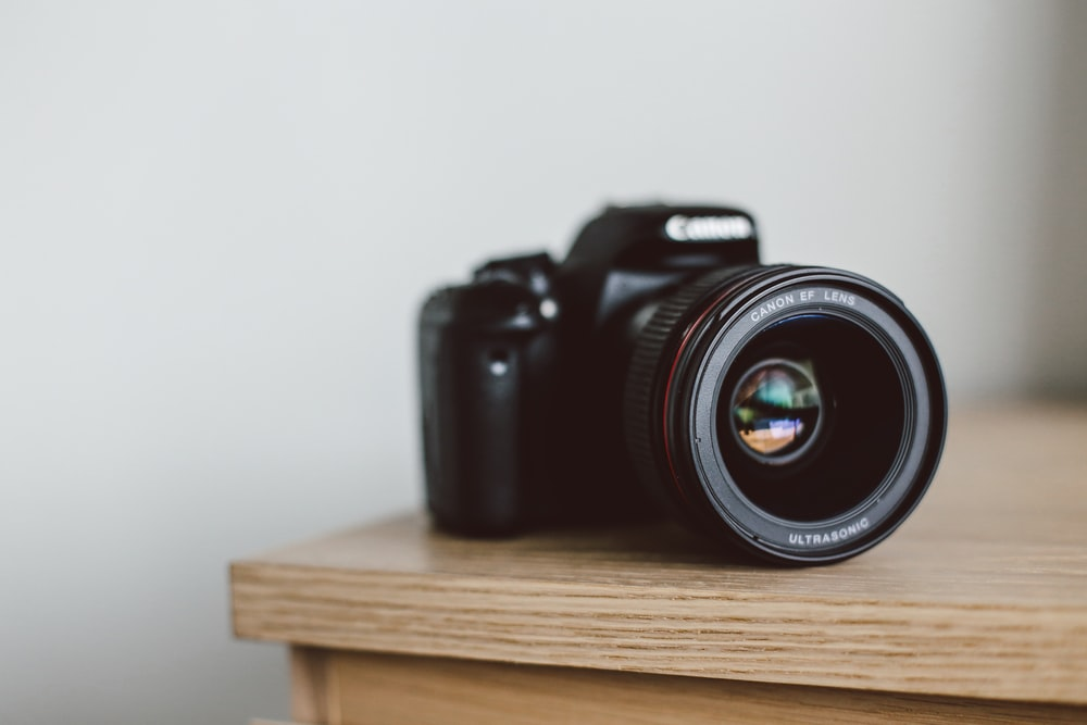 selective focus photo of black Canon DSLR camera on table