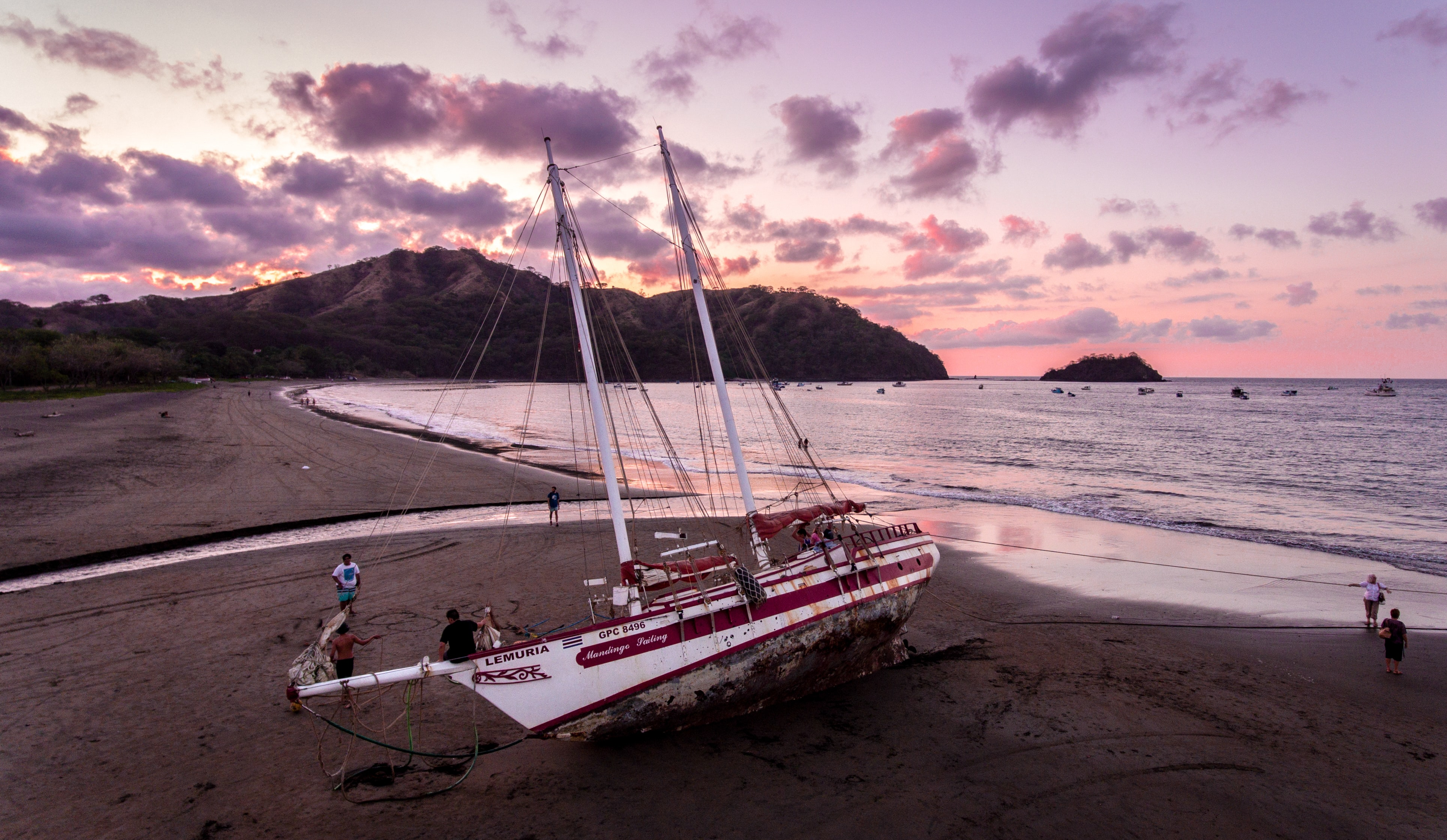white and red sail boat on seashore