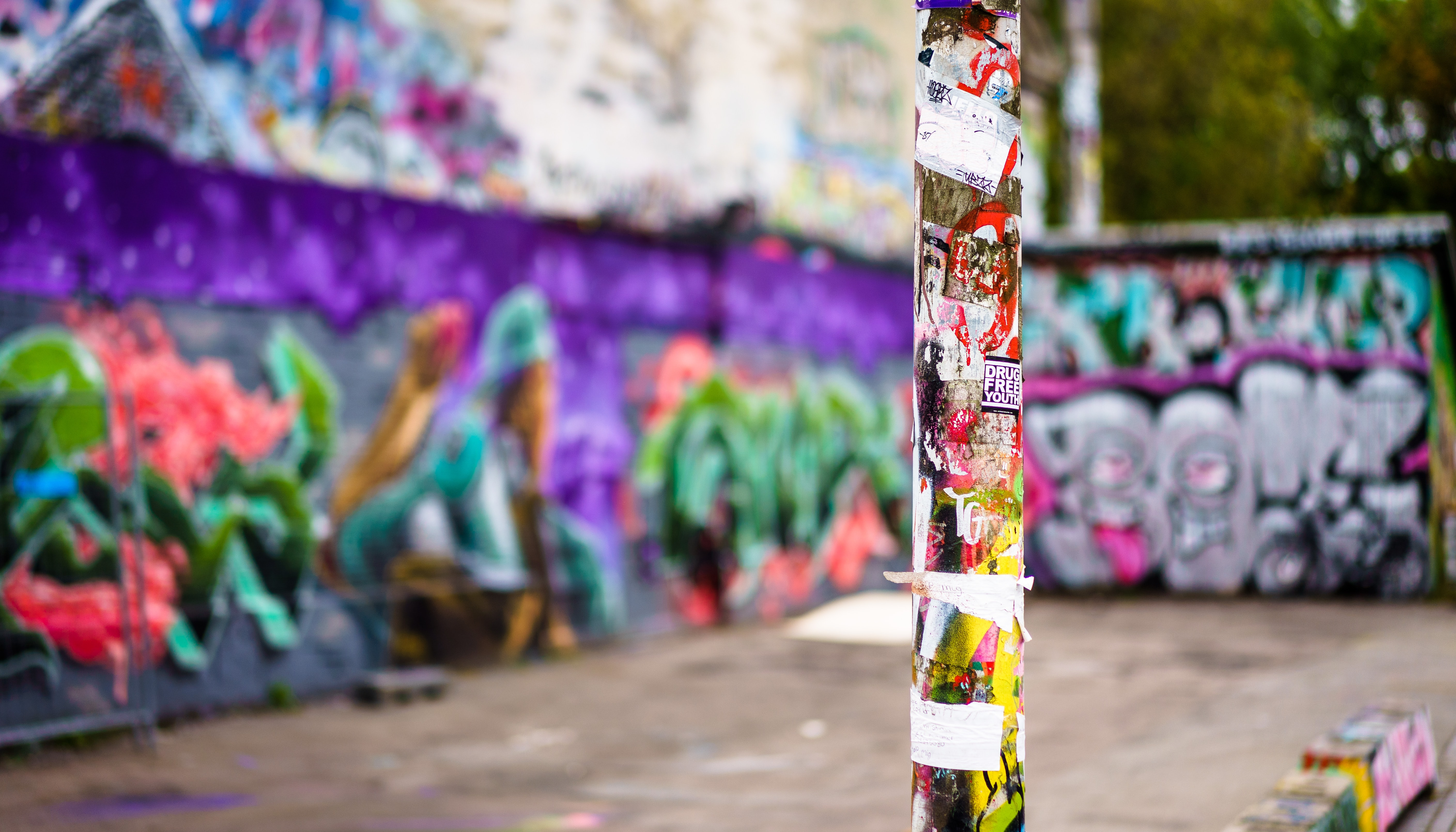 Focused pole covered in graffiti and stickers in Freetown Christiania with colorful background graffiti