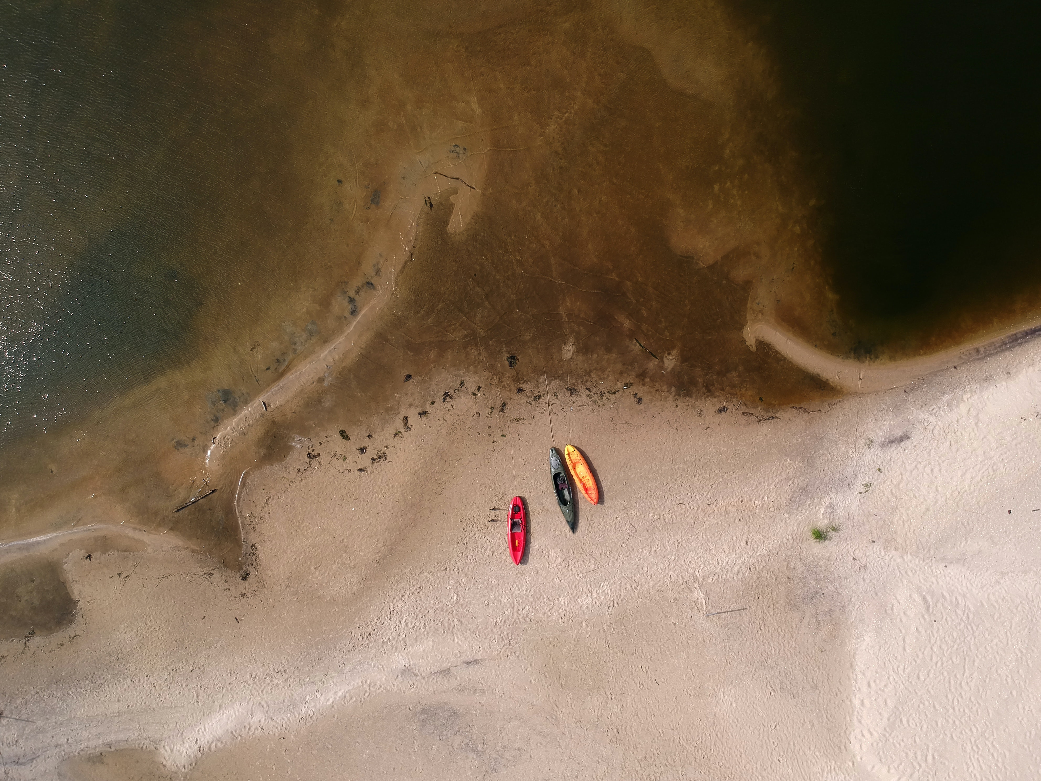 aerial photography of three kayaks near body of water