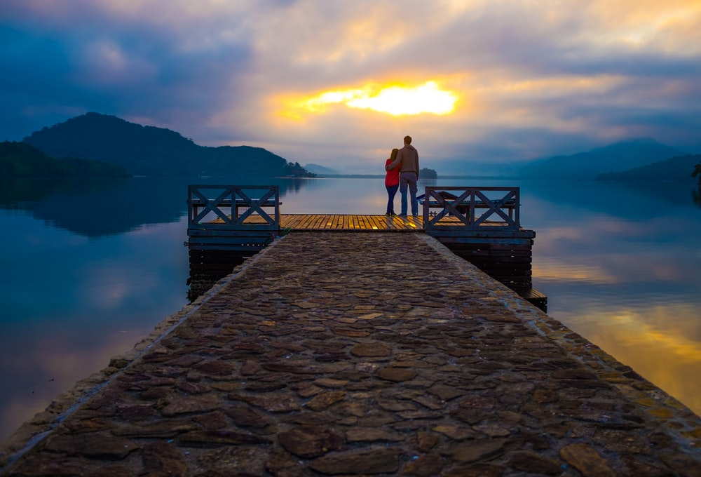 couple standing on dock looking at sunset