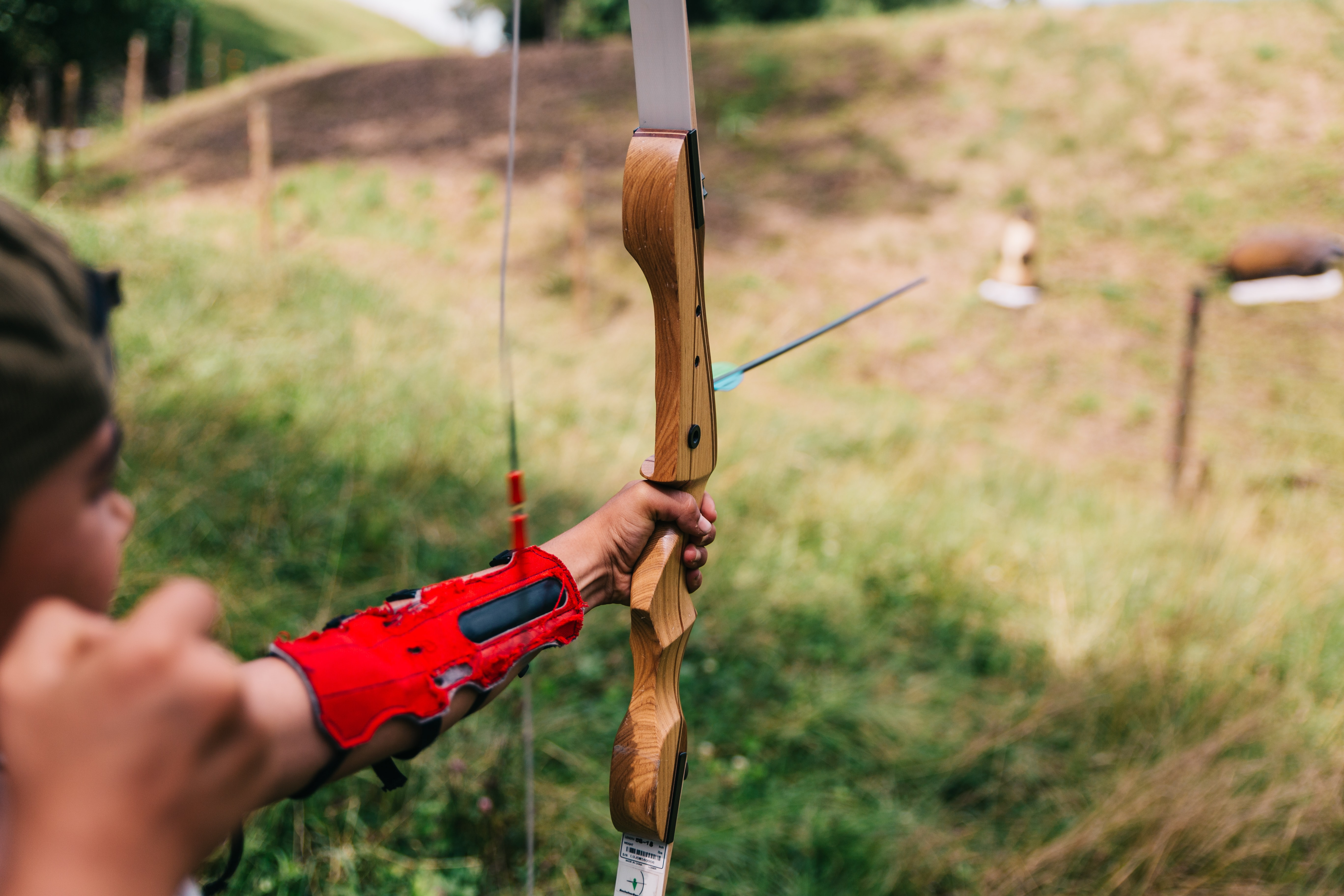Person holds bow and arrow and aims at target