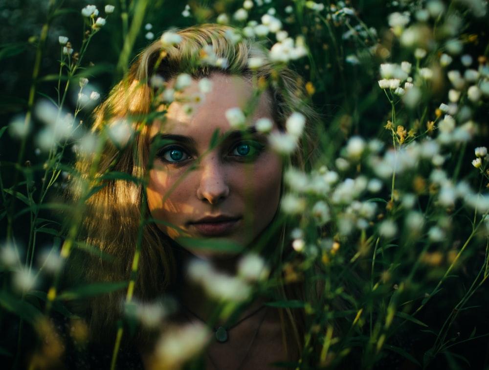 woman behind white petaled flowers