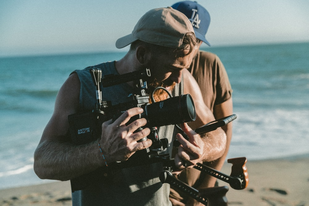 man holding video camera standing near body of water