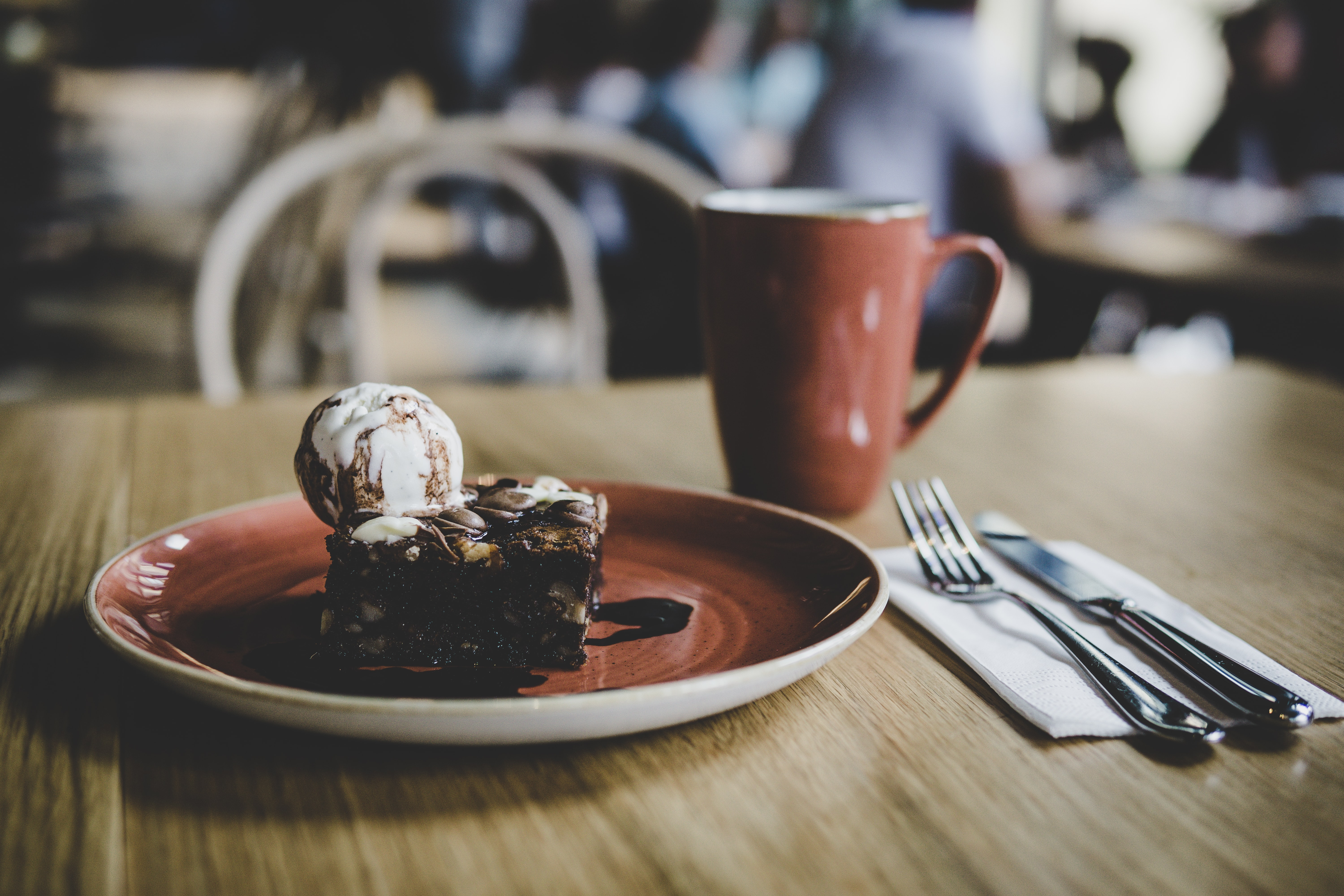 A chocolate nut brownie topped with vanilla ice cream and chocolate syrup beside a mug of coffee and cutlery on a wooden table