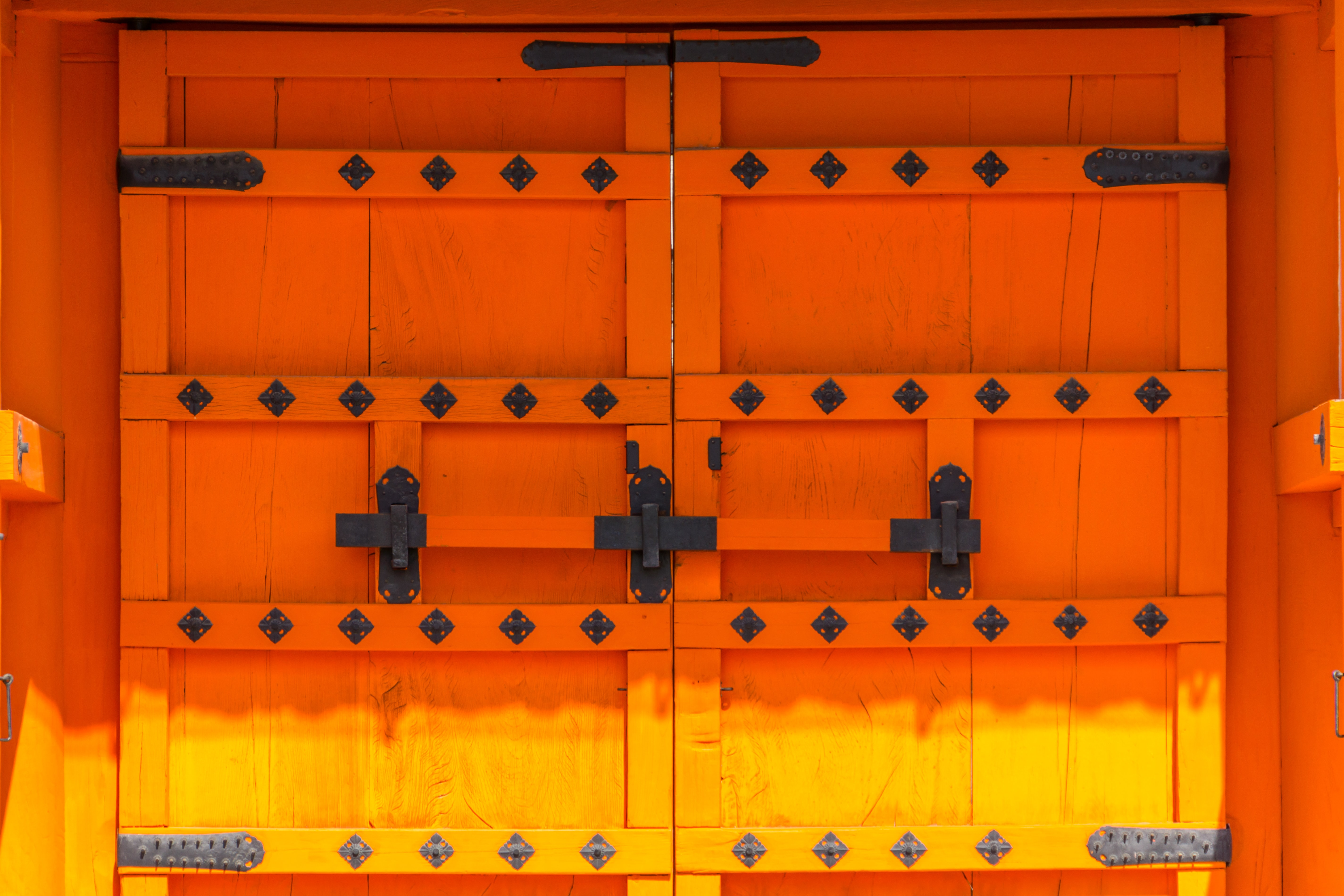 Ancient japanese wooden door entrance with designs and a wooden bar