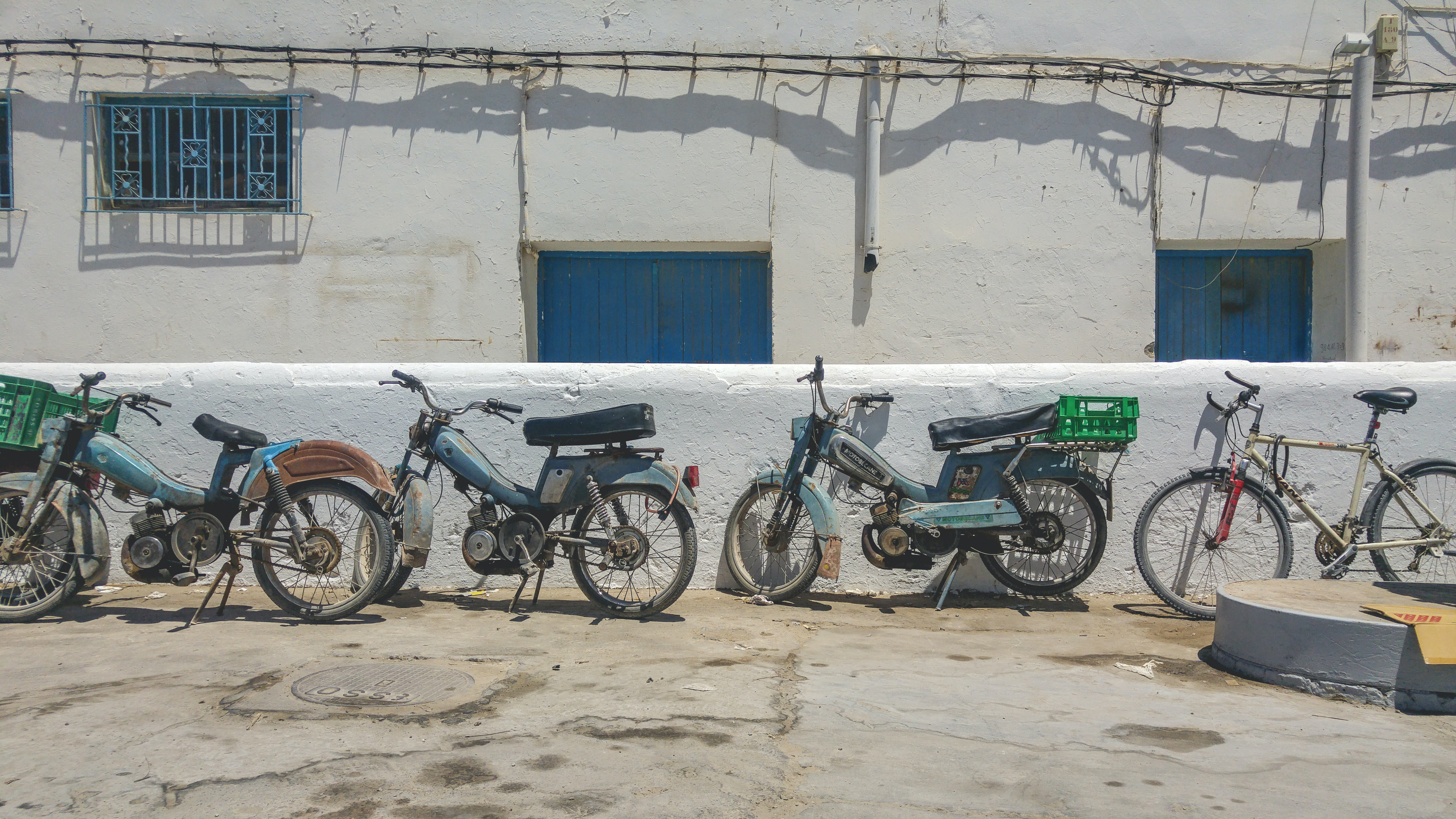 A row of old fashioned motorcycles beside a bike lined up against the wall in a rural area