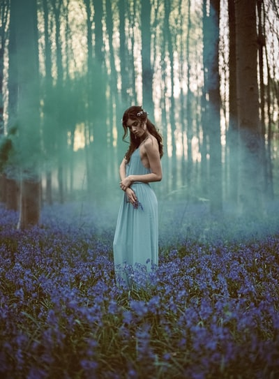 woman in blue spaghetti strap dress standing in the middle of forest