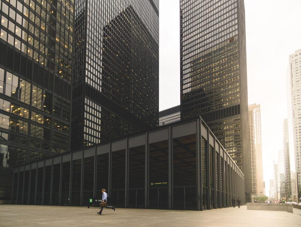 man walking along high-rise building