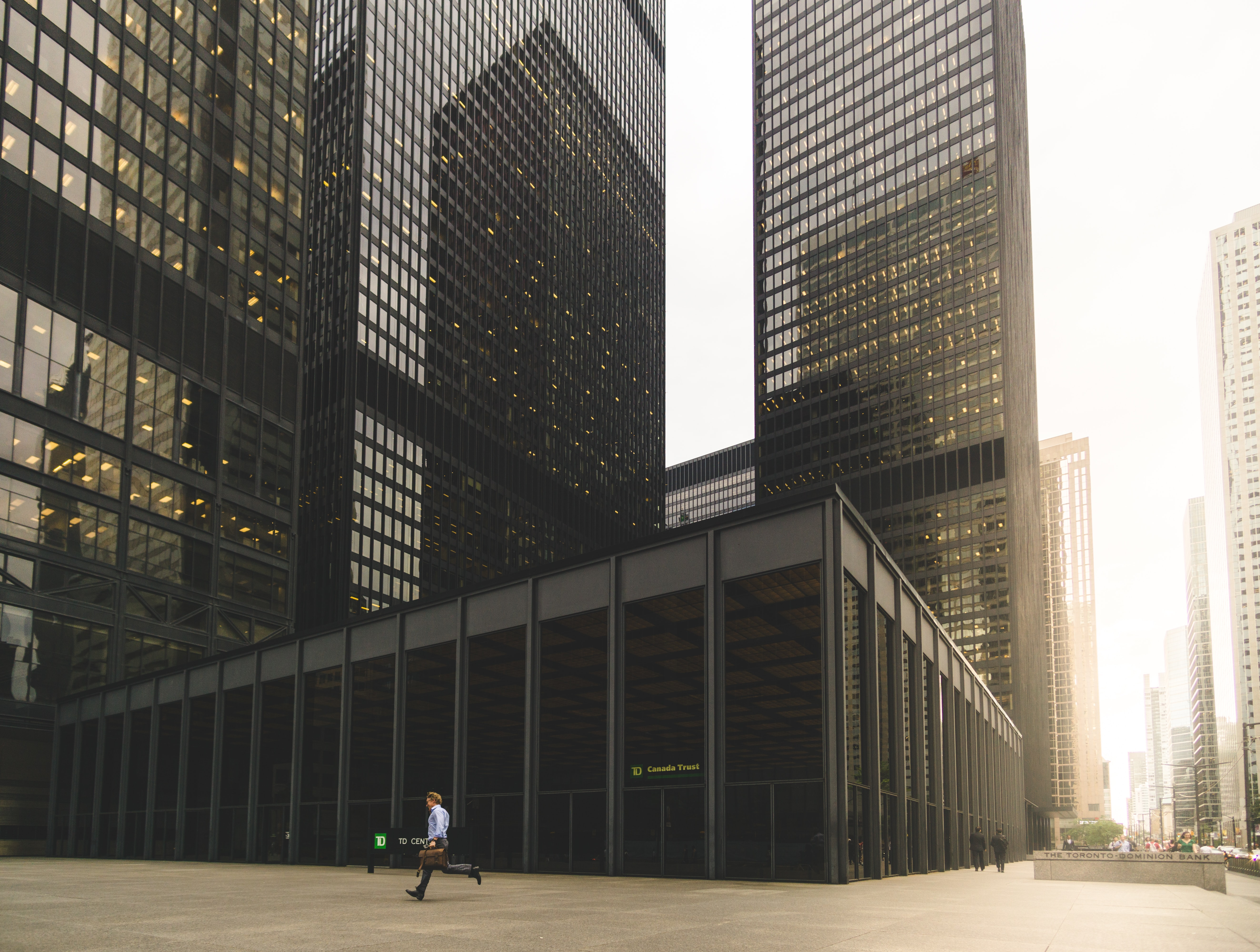 A man with a leather suitcase running near an office building