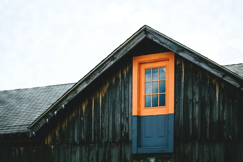 orange and black wooden door on top of house