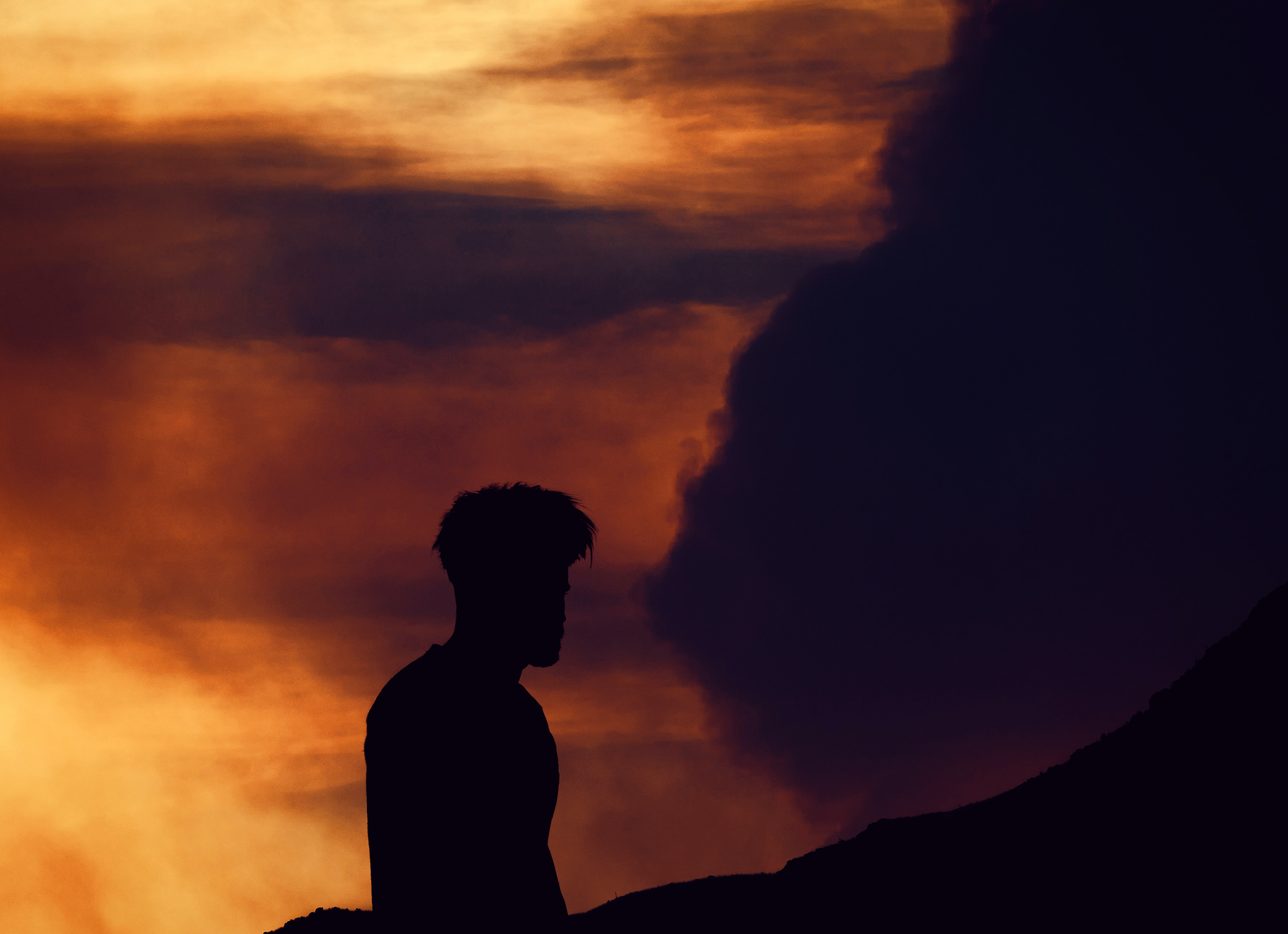 silhouette photo of man near body of water