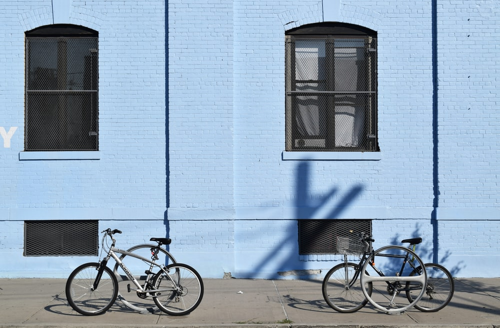 two bicycles parked in front of blue building