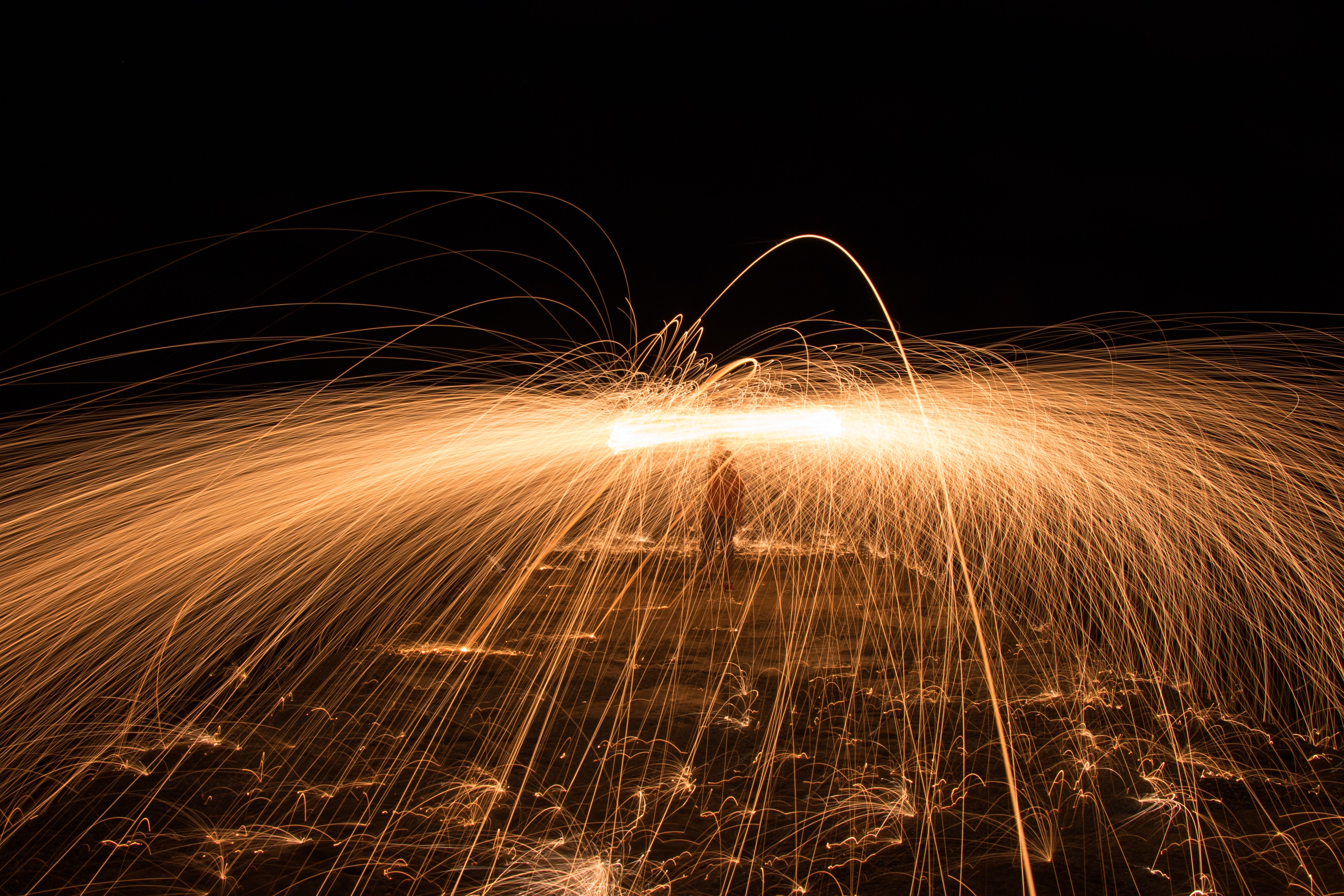 time-lapse photography of person using lit steel wool