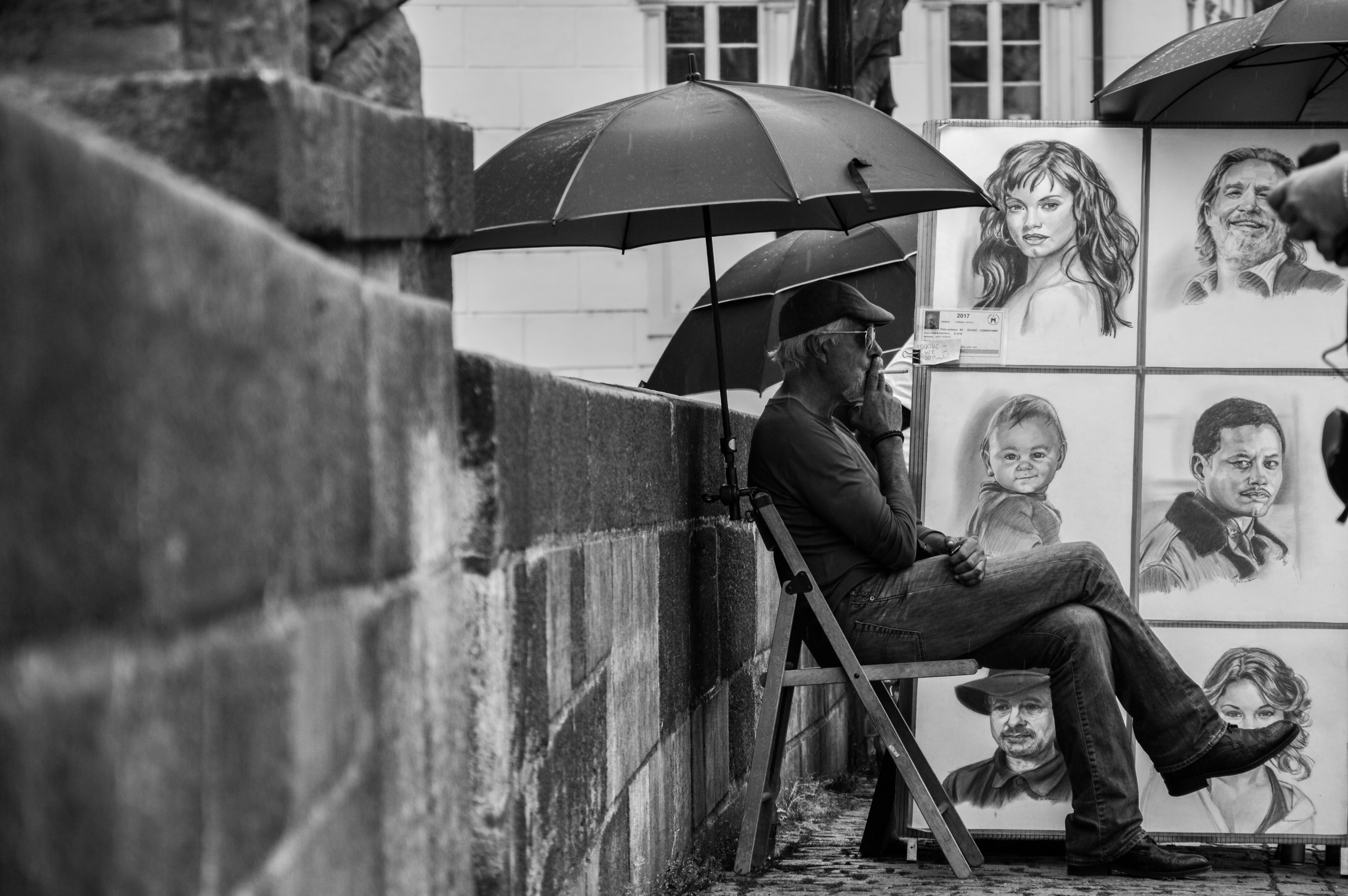 Black and white photo of man smoking under umbrella next to hand drawings in Prague