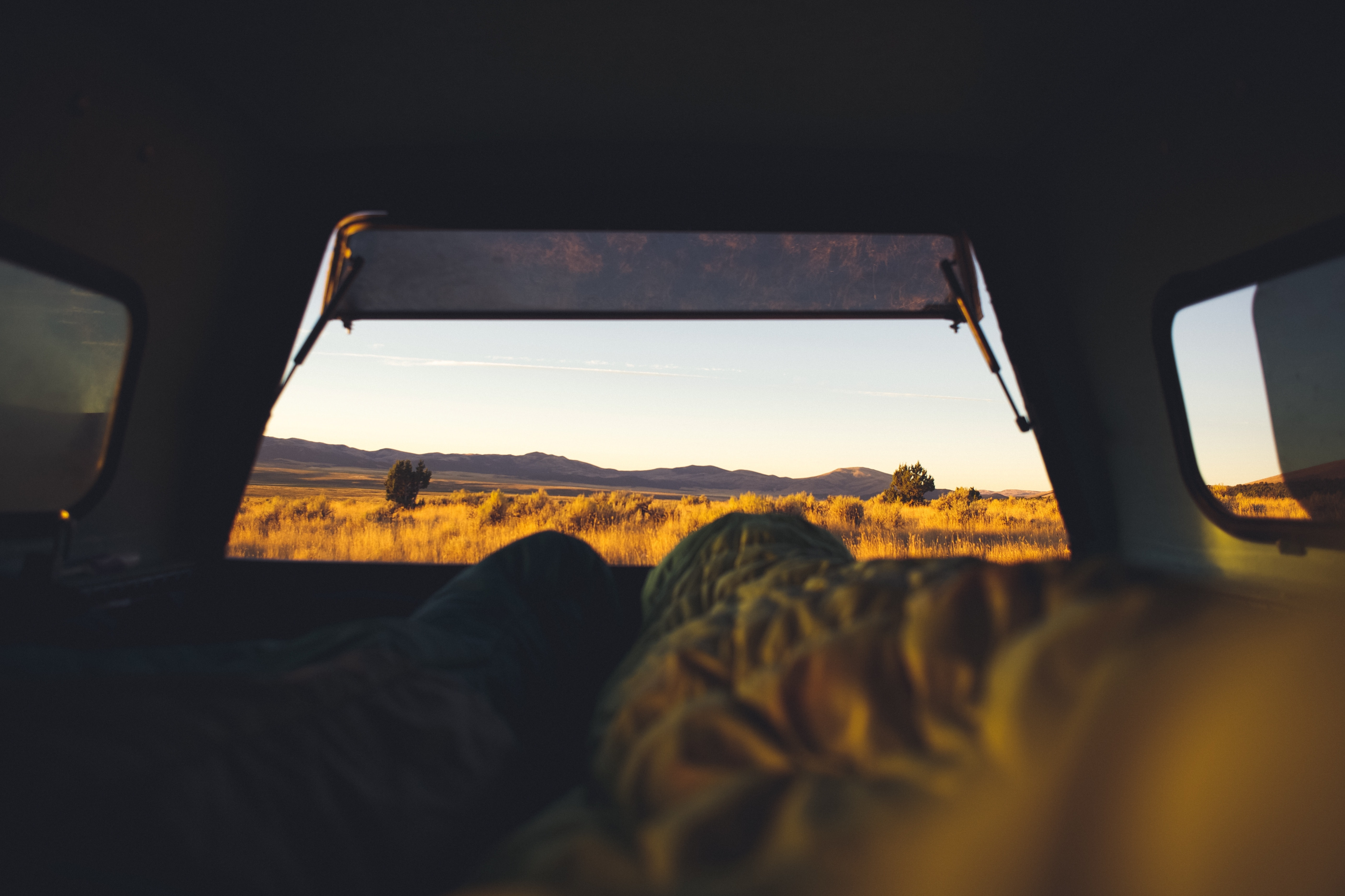Two campers lying in the back of an off-road vehicle parked in the middle of the wilderness