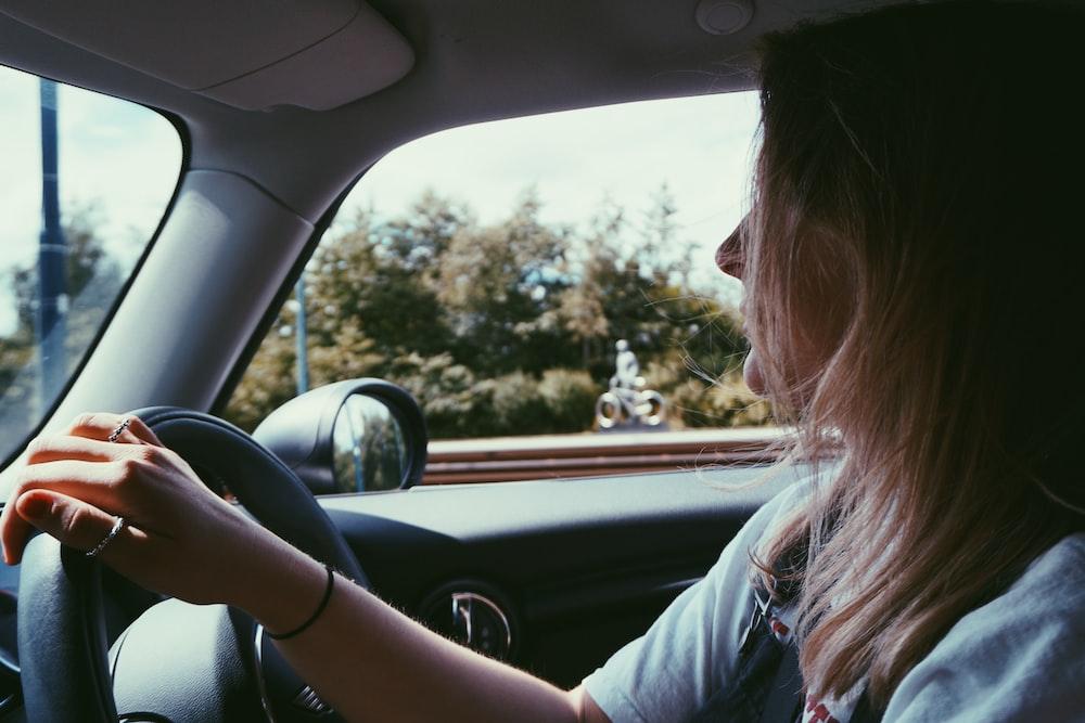 woman holding steering wheel in car
