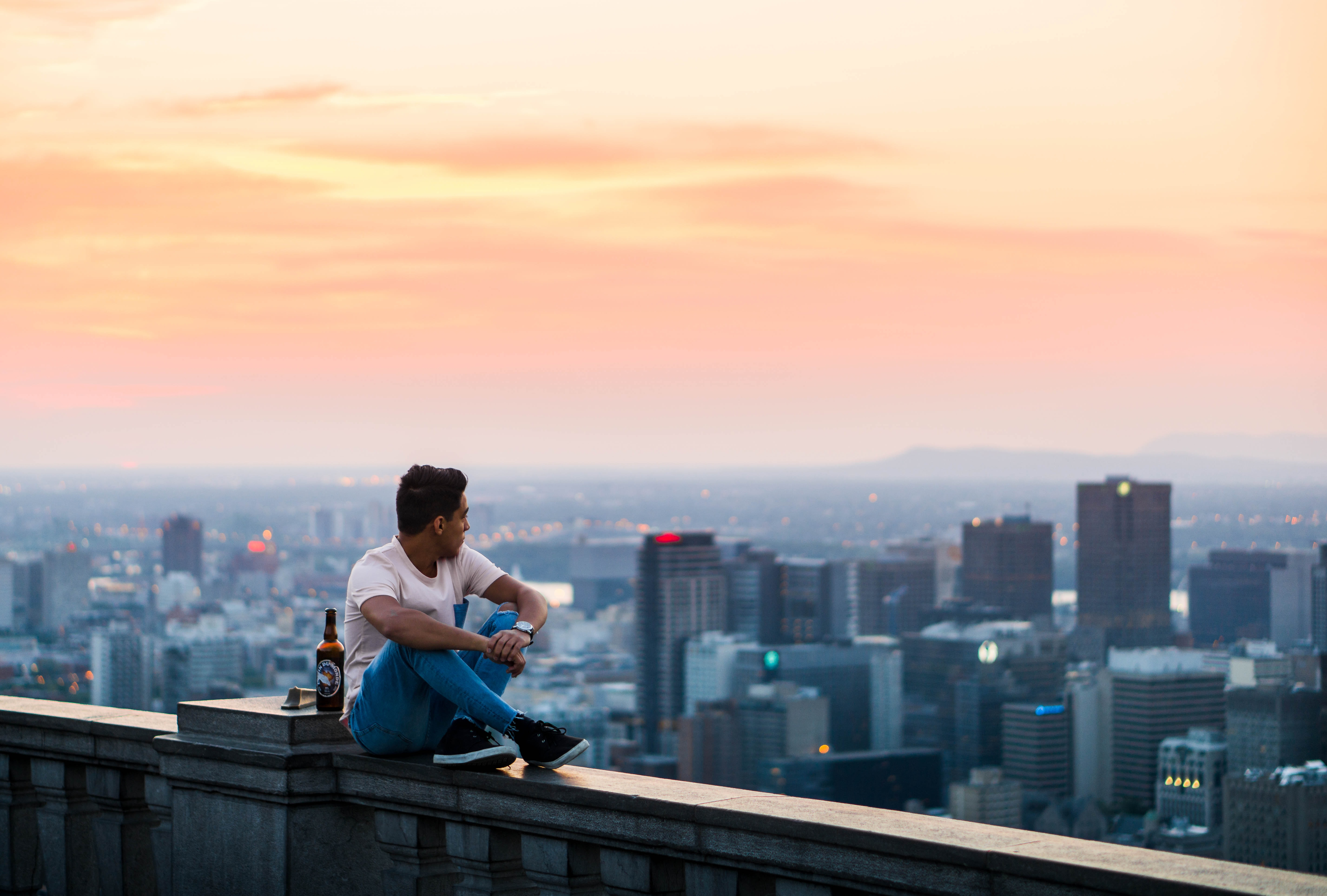Man sitting on ledge of a skyscraper at sunset viewing the cityscape of Chalet du Mont-Royal