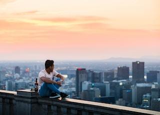 man seating beside buildings