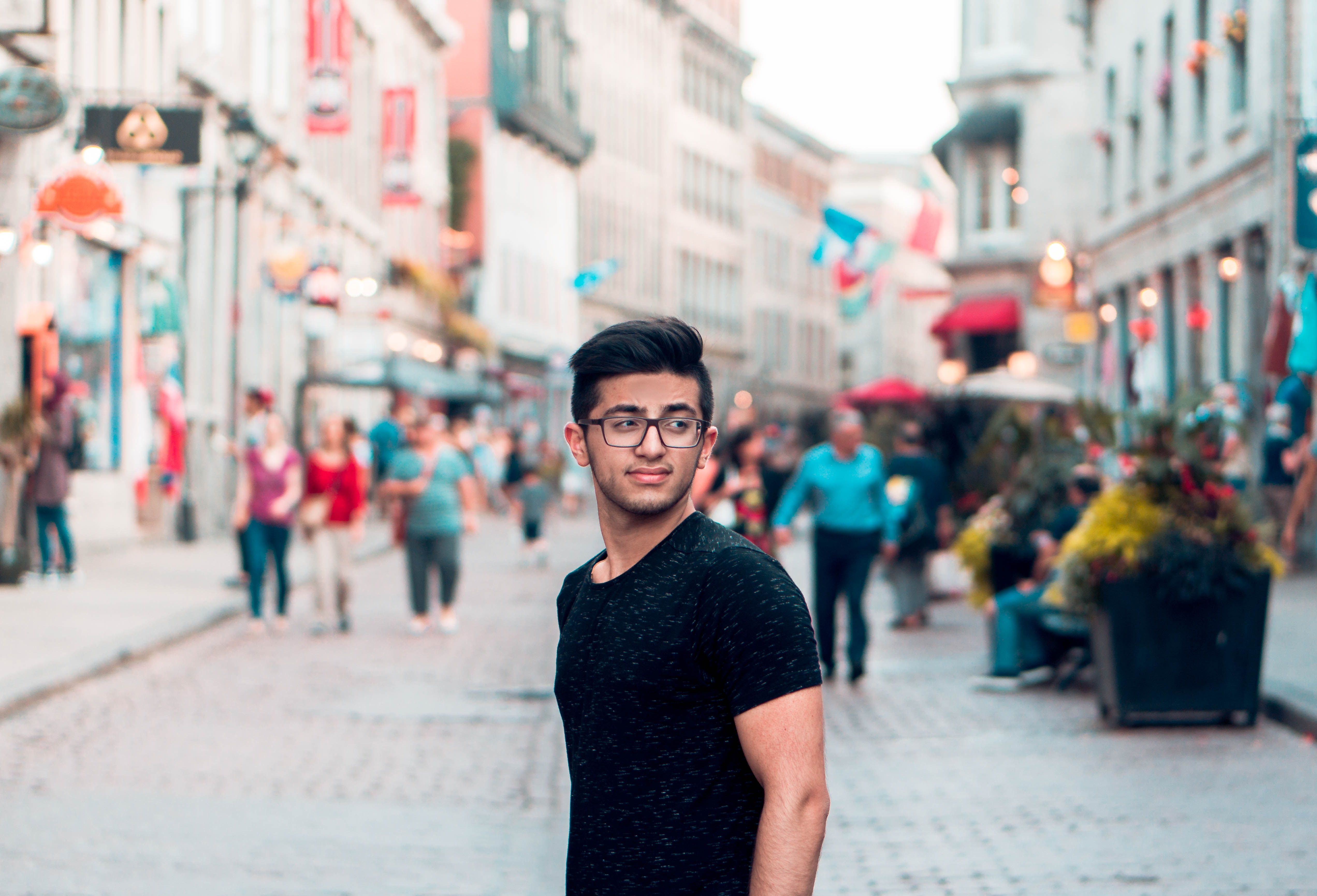 A young man in glasses on a paved street in Montreal