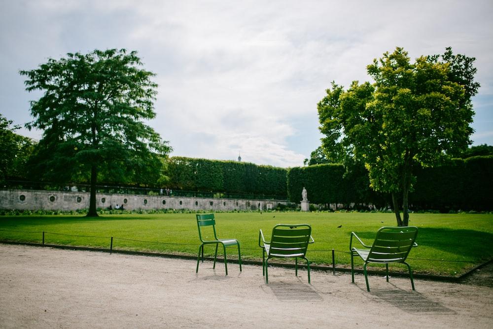three green steel chairs near green field