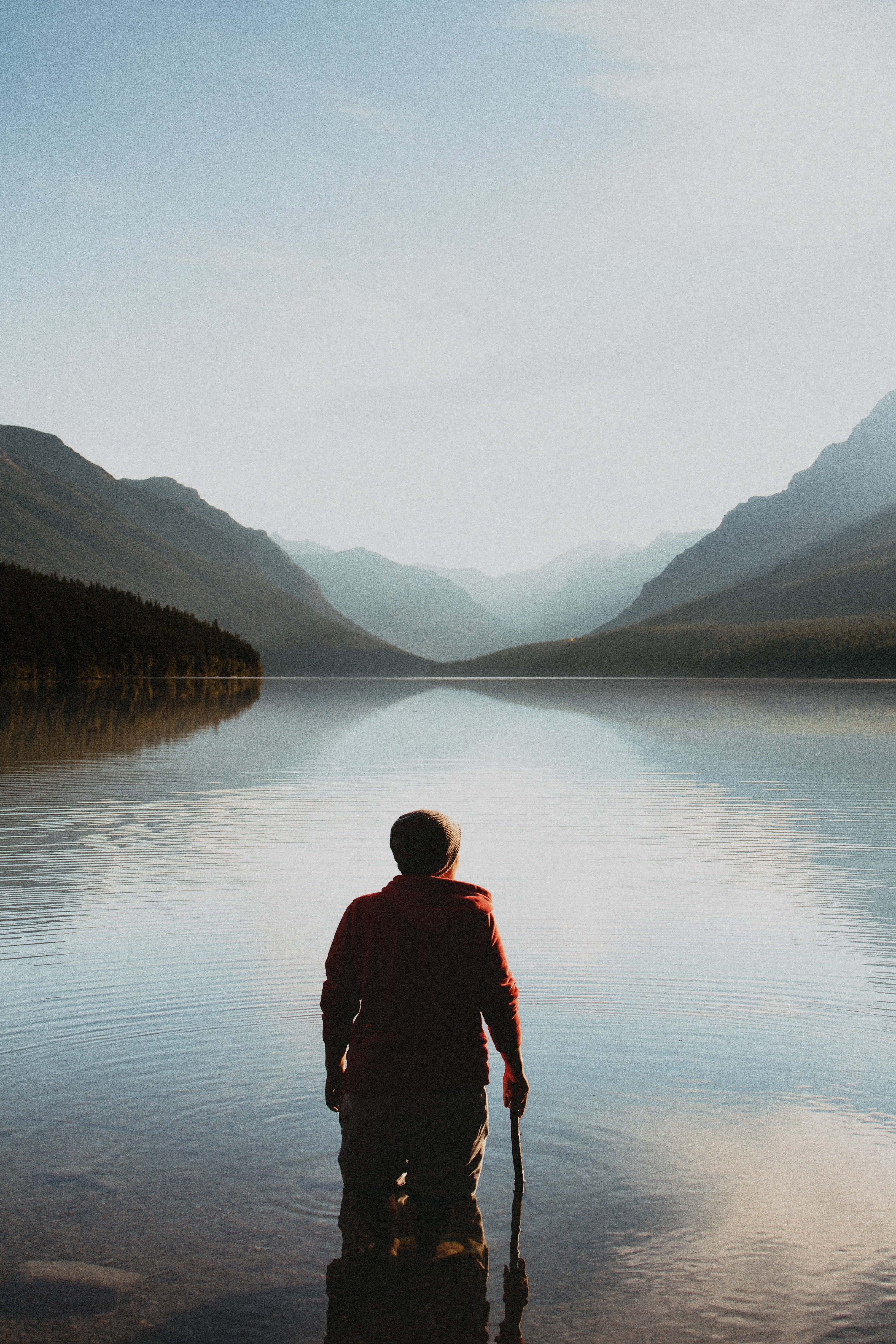 person standing on the lake in the middle of mountains