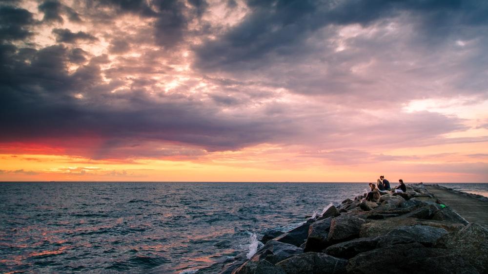 people sitting on rock near body of water