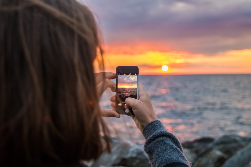 woman holding phone taking a photo of sunset