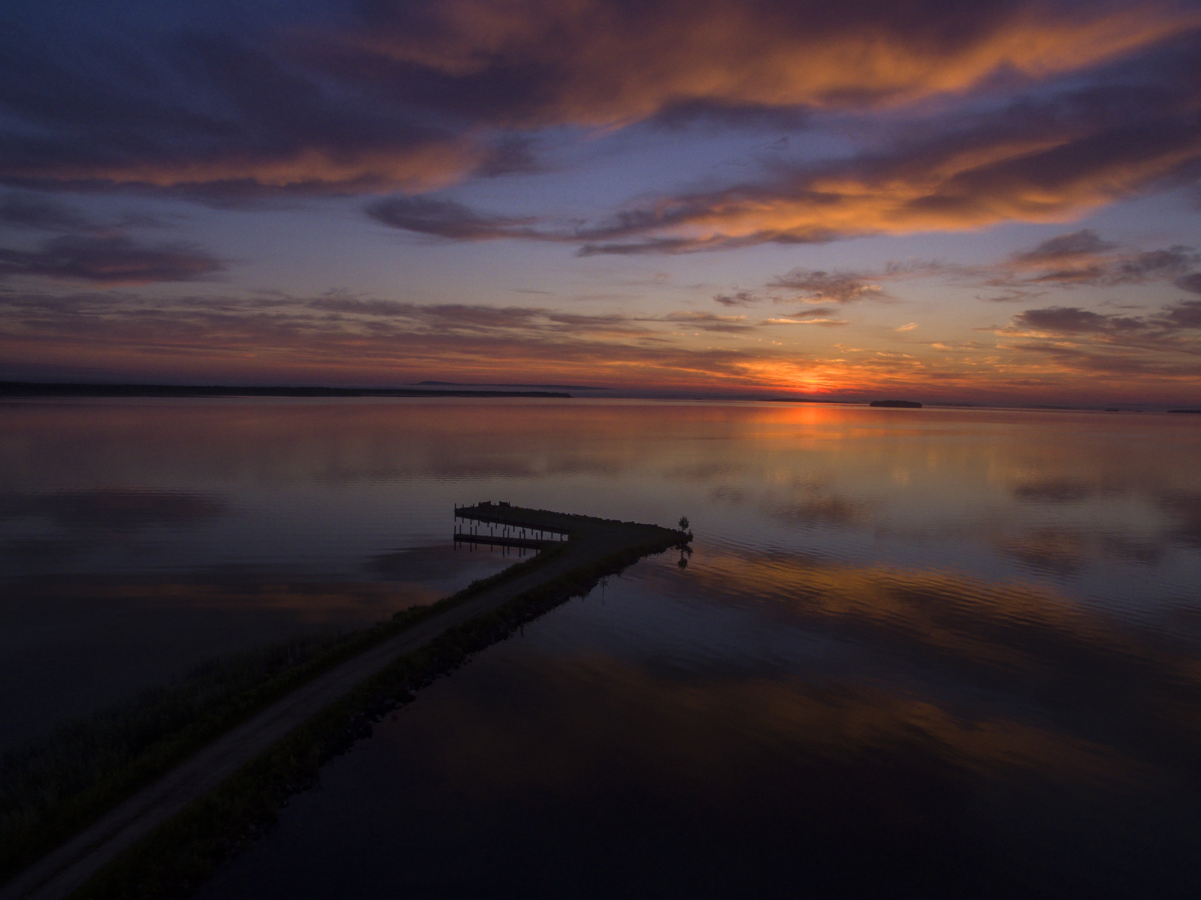 View of a coastline in Michigan with a colorful sunrise at the horizon