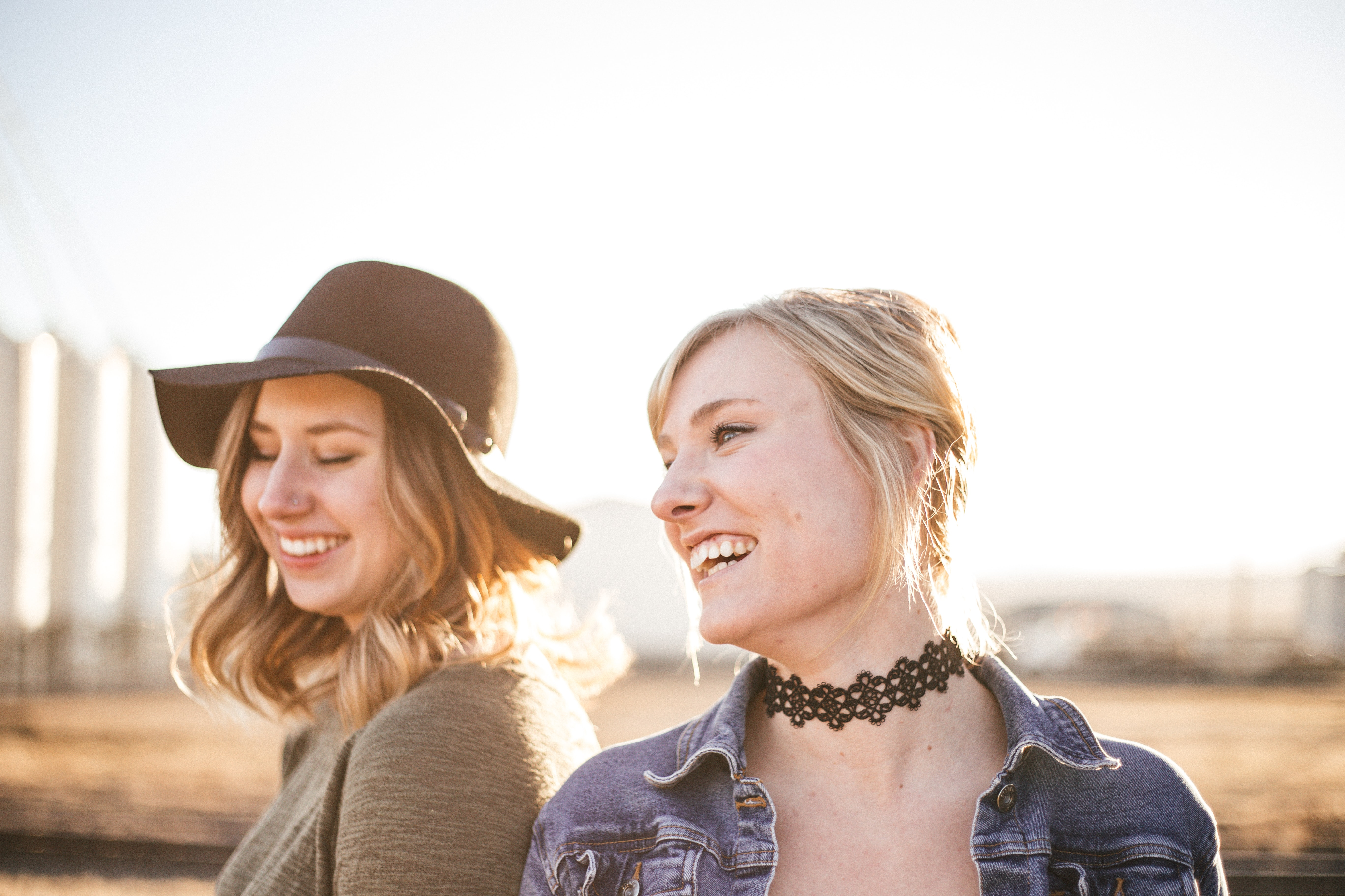 Two women in a hat and choker stand closely, laughing, against a blurry outdoor background