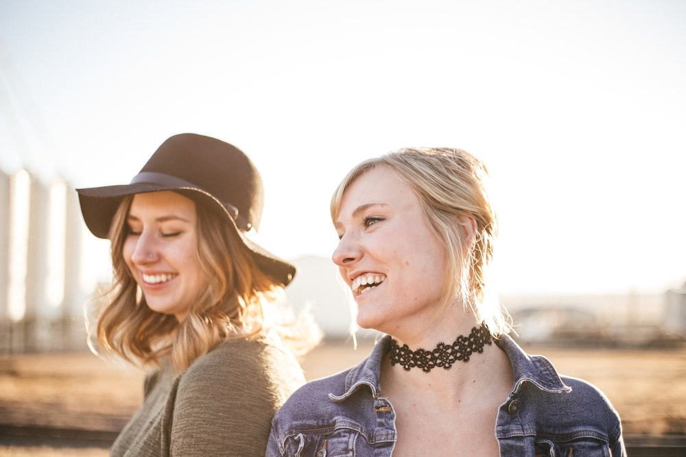 two woman taking a sideview selfie