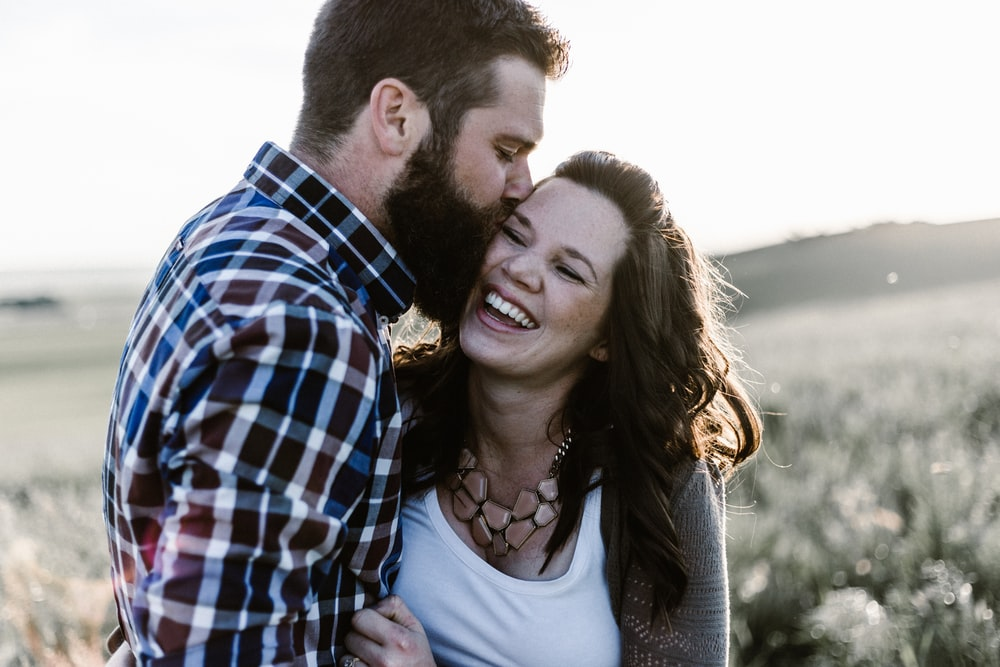 man kissing woman in grass area