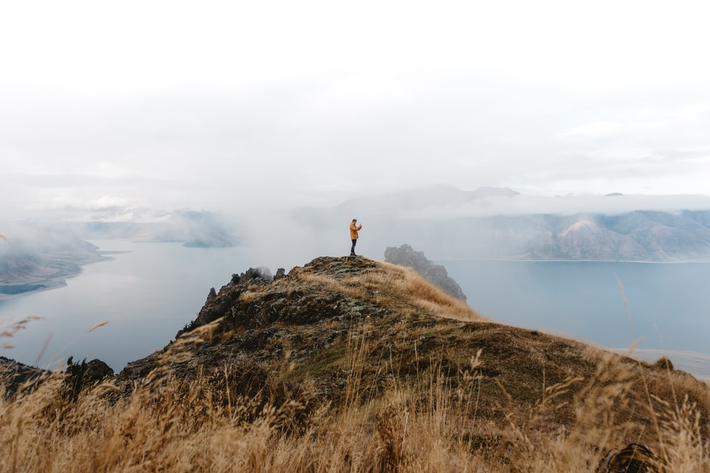 person standing on top of hill near lake during daytime
