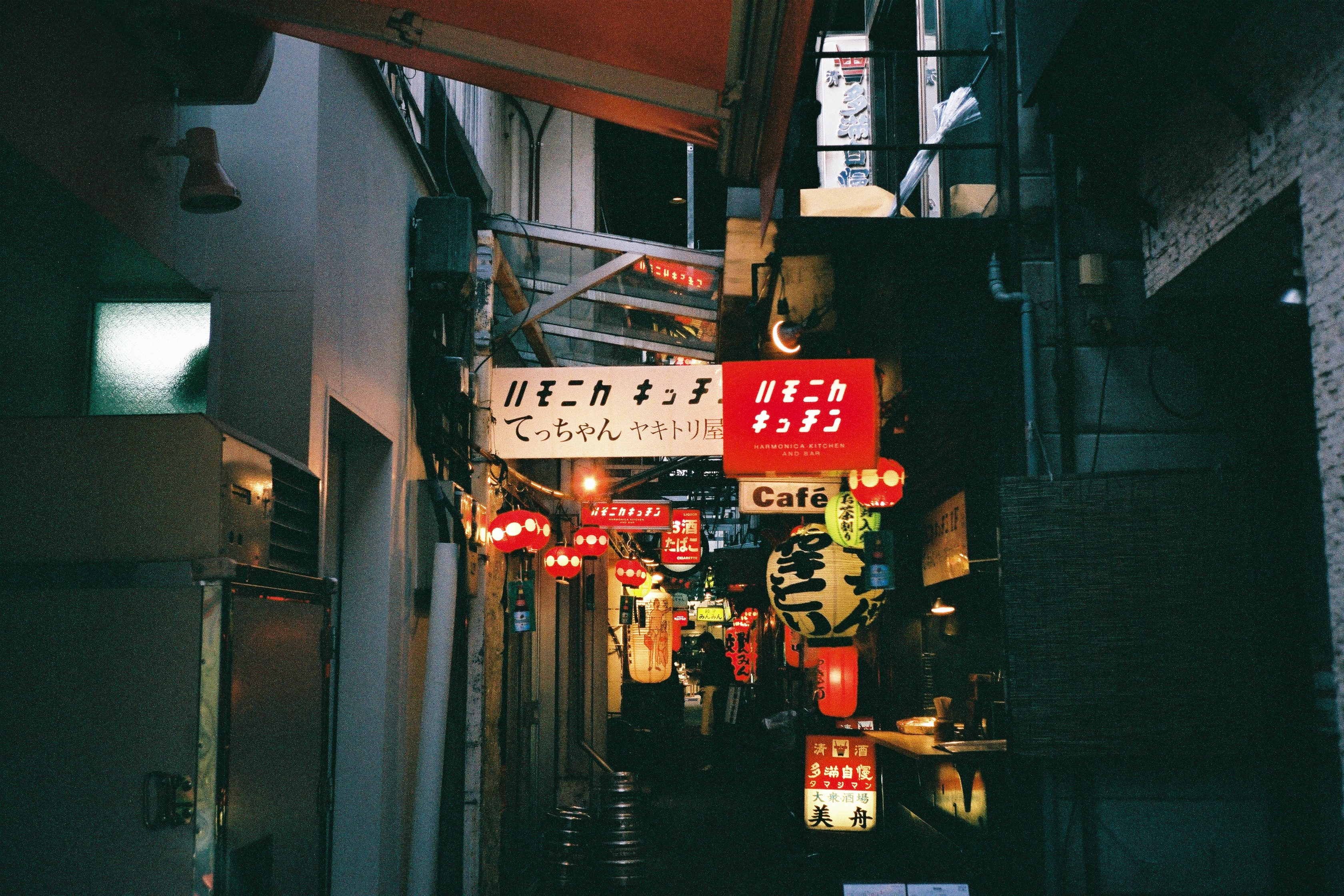 A busy Japanese marketplace street at night lit up with shop signs