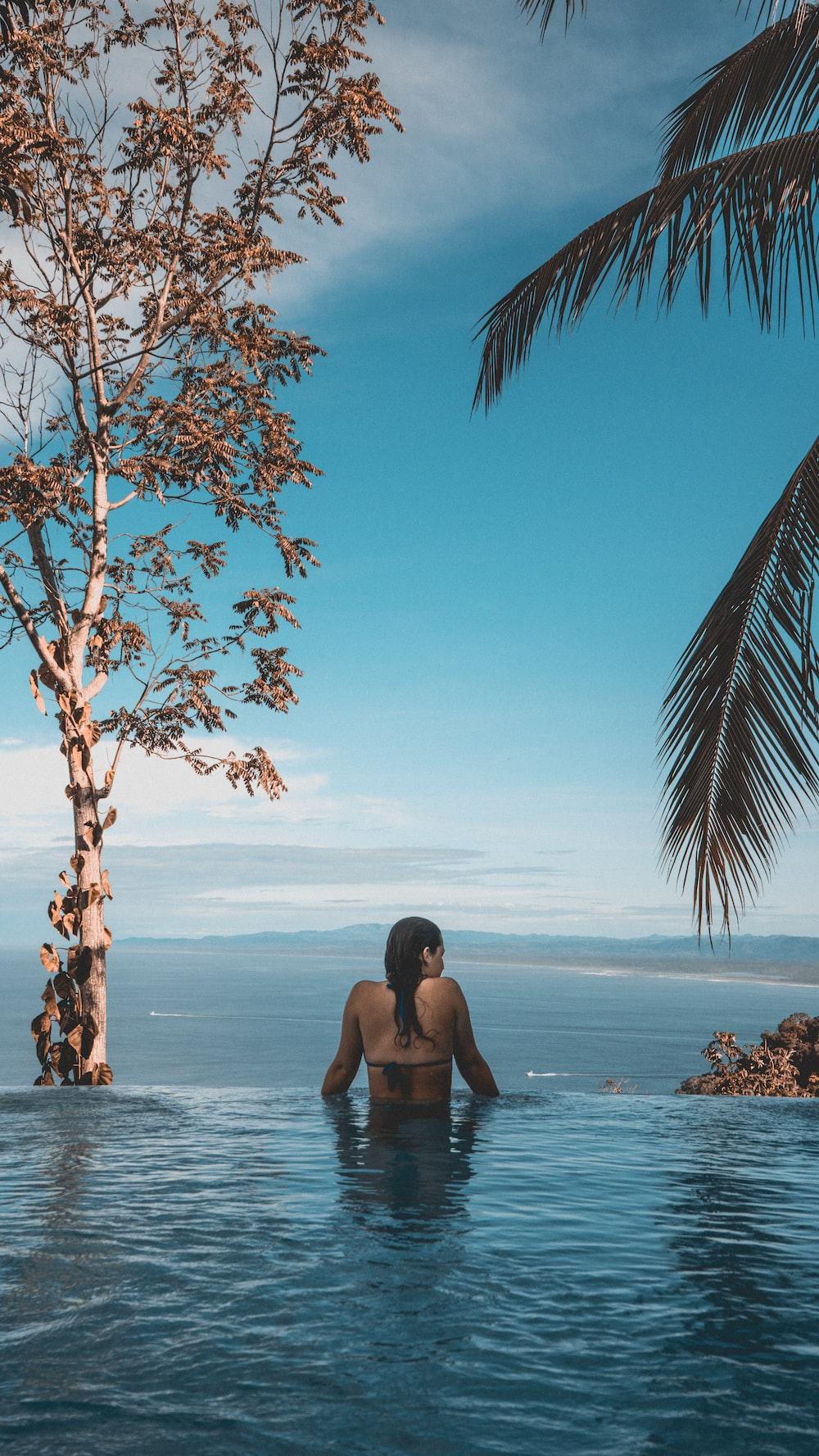 woman wearing black bikini tap swimming on body of water between trees