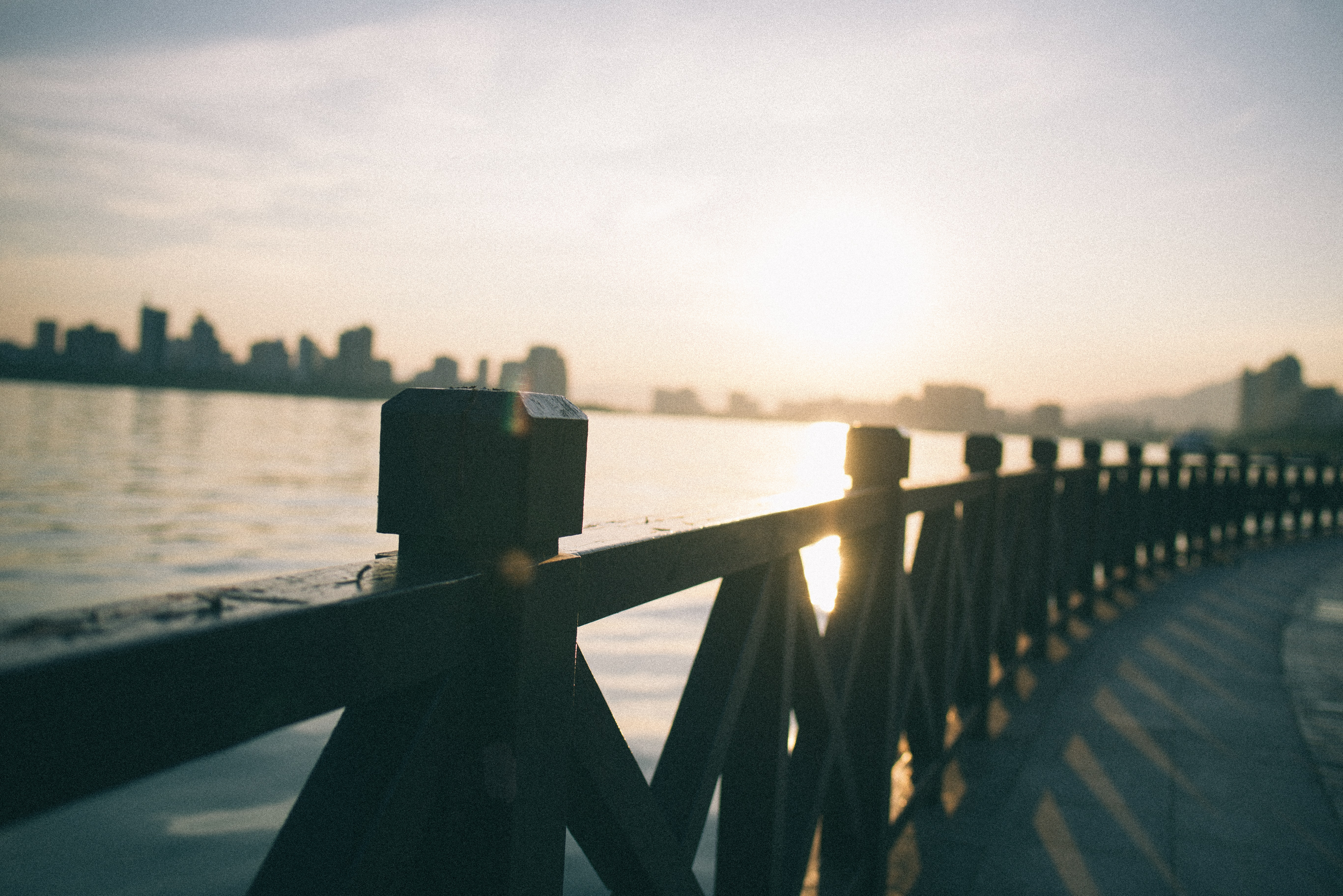 brown wooden dock railings with body of water background