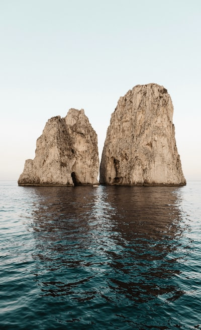 two beige rock formations on body of water