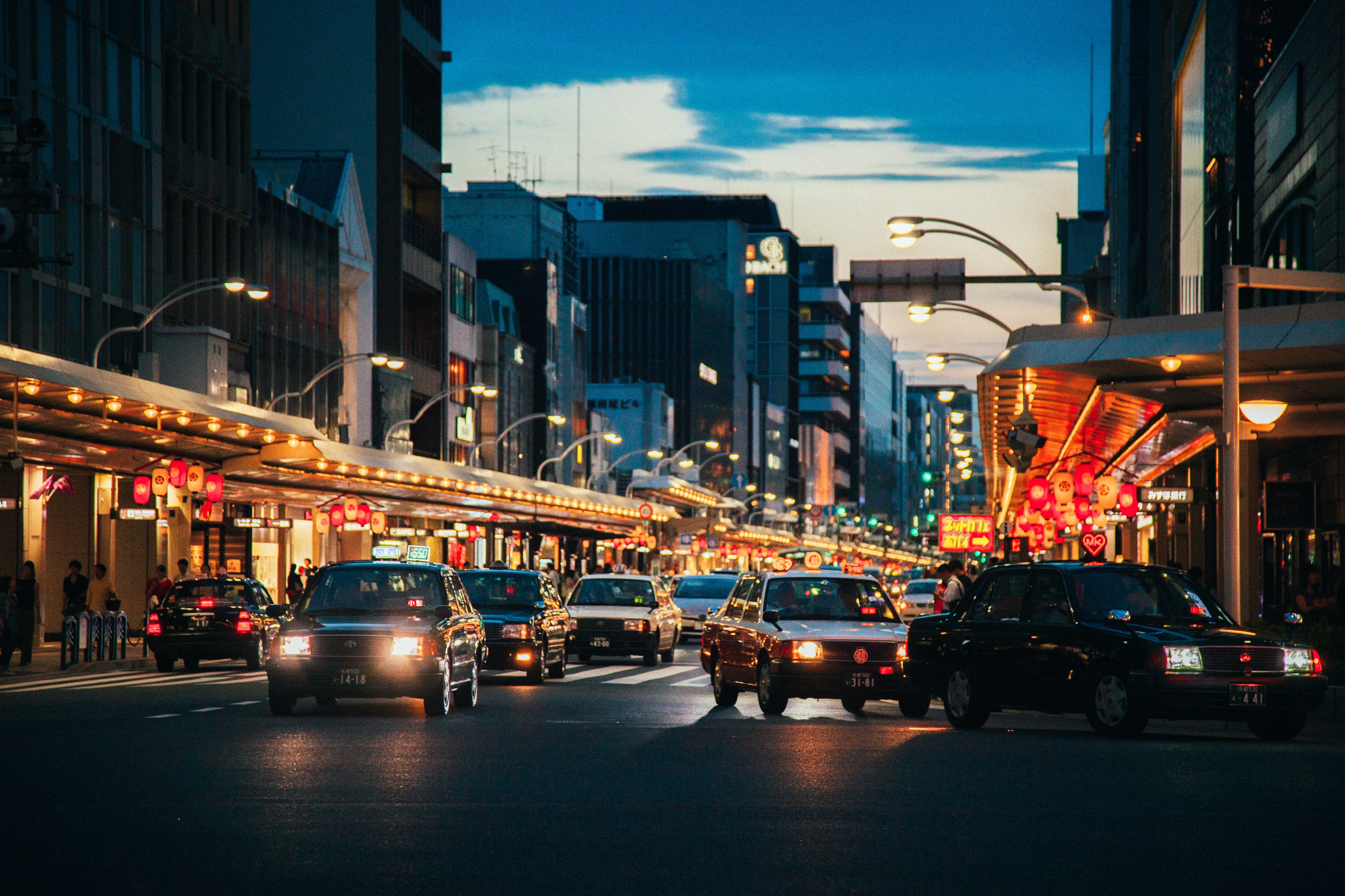 Cars in a busy street illuminated by lights from stores and bars in Kyoto