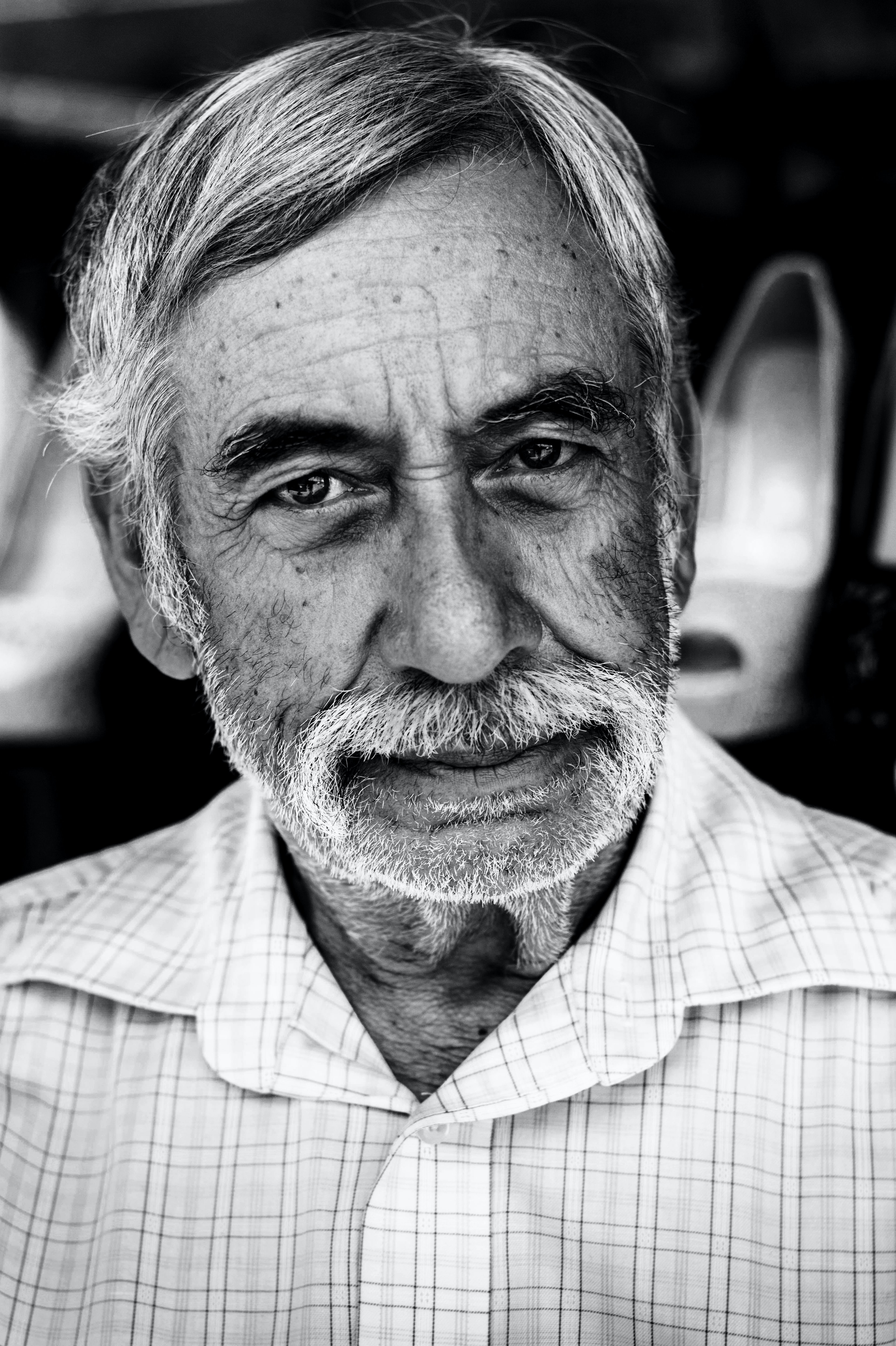 Black and white close up shot of grey bearded older man with relaxed expression