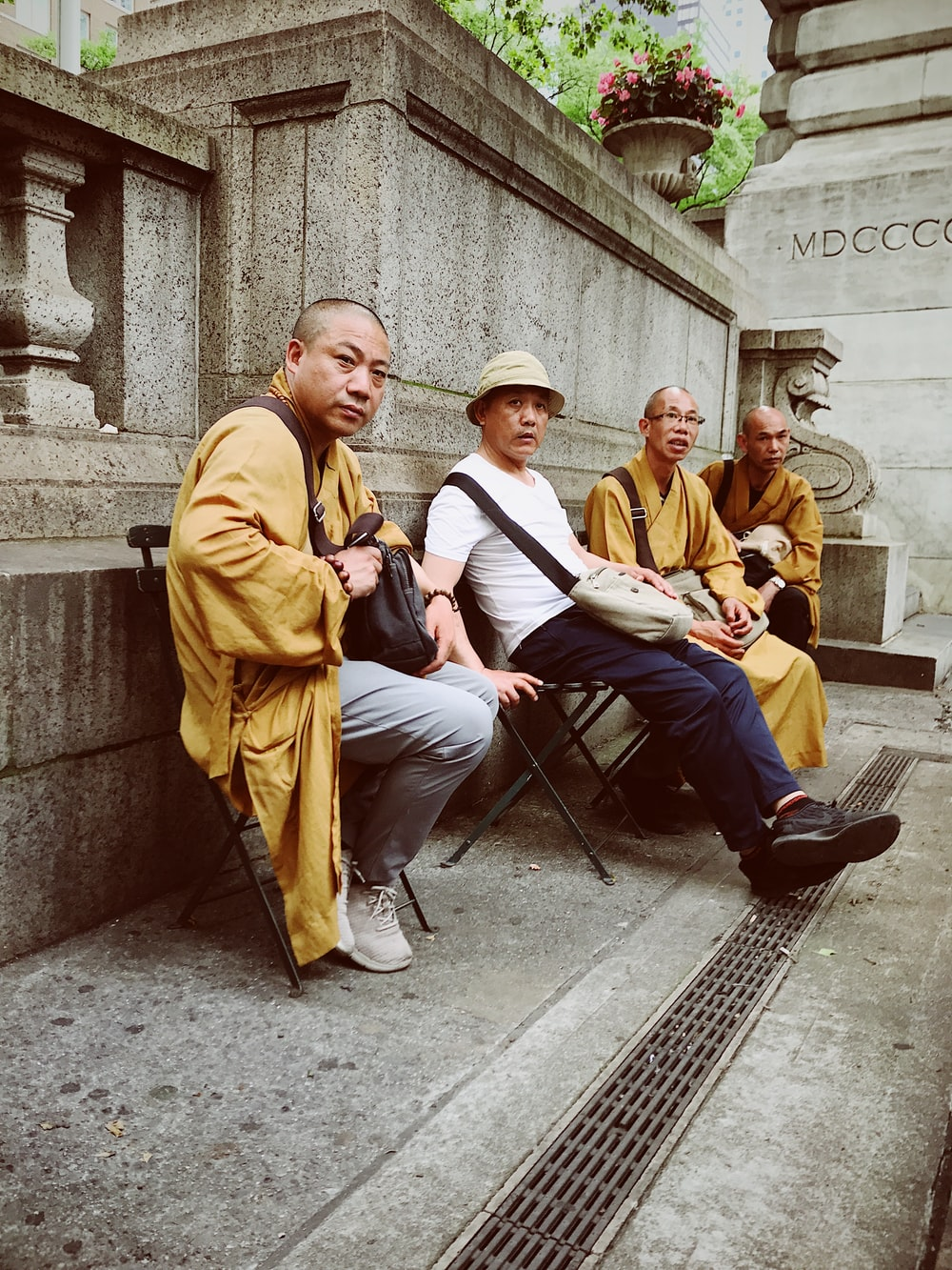 four men sitting on chairs outdoor during daytime