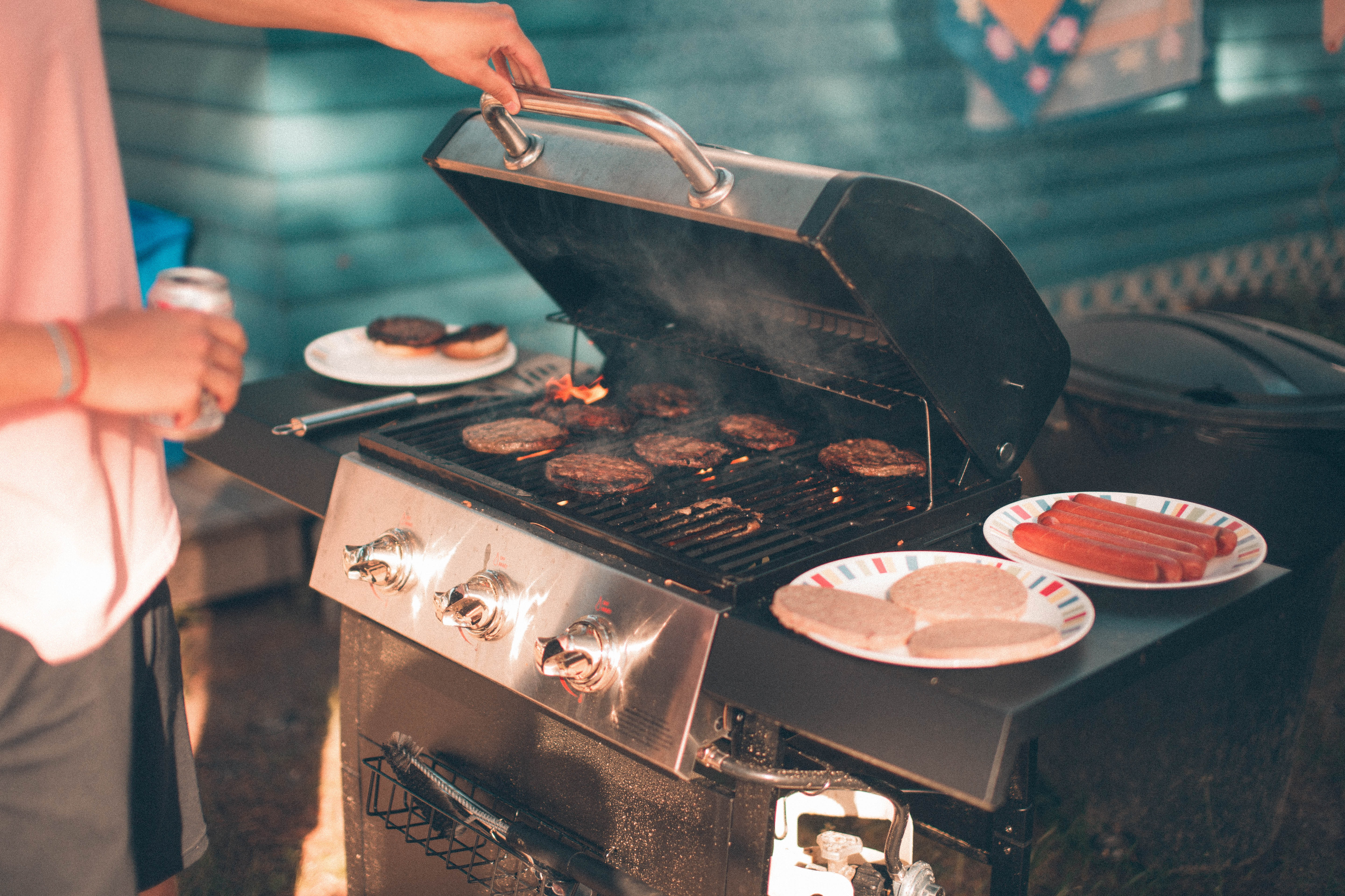 person cooking burger on gas grill
