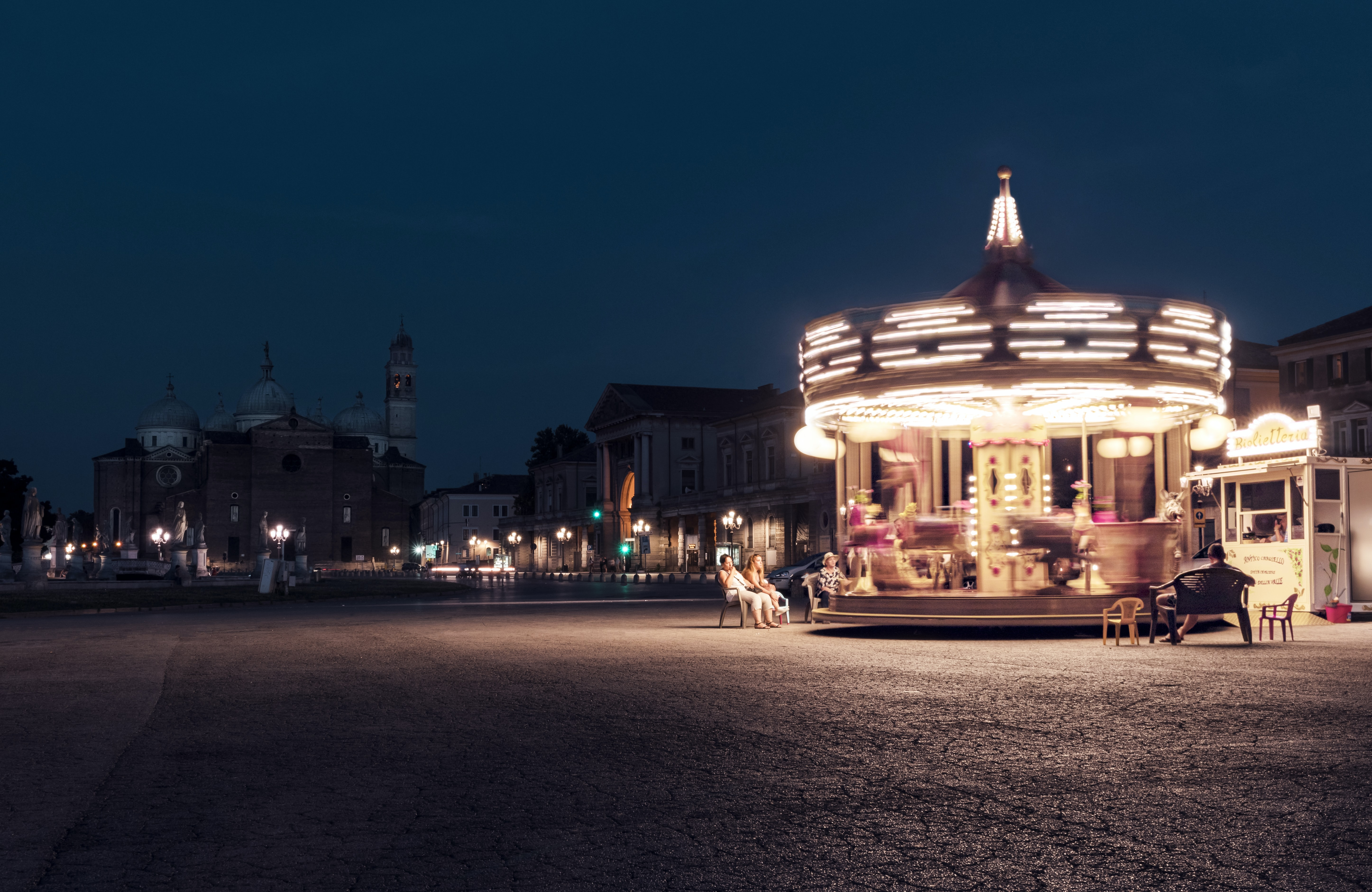 Adults watching a bright spinning carousel in the streets of Prato della Valle at night