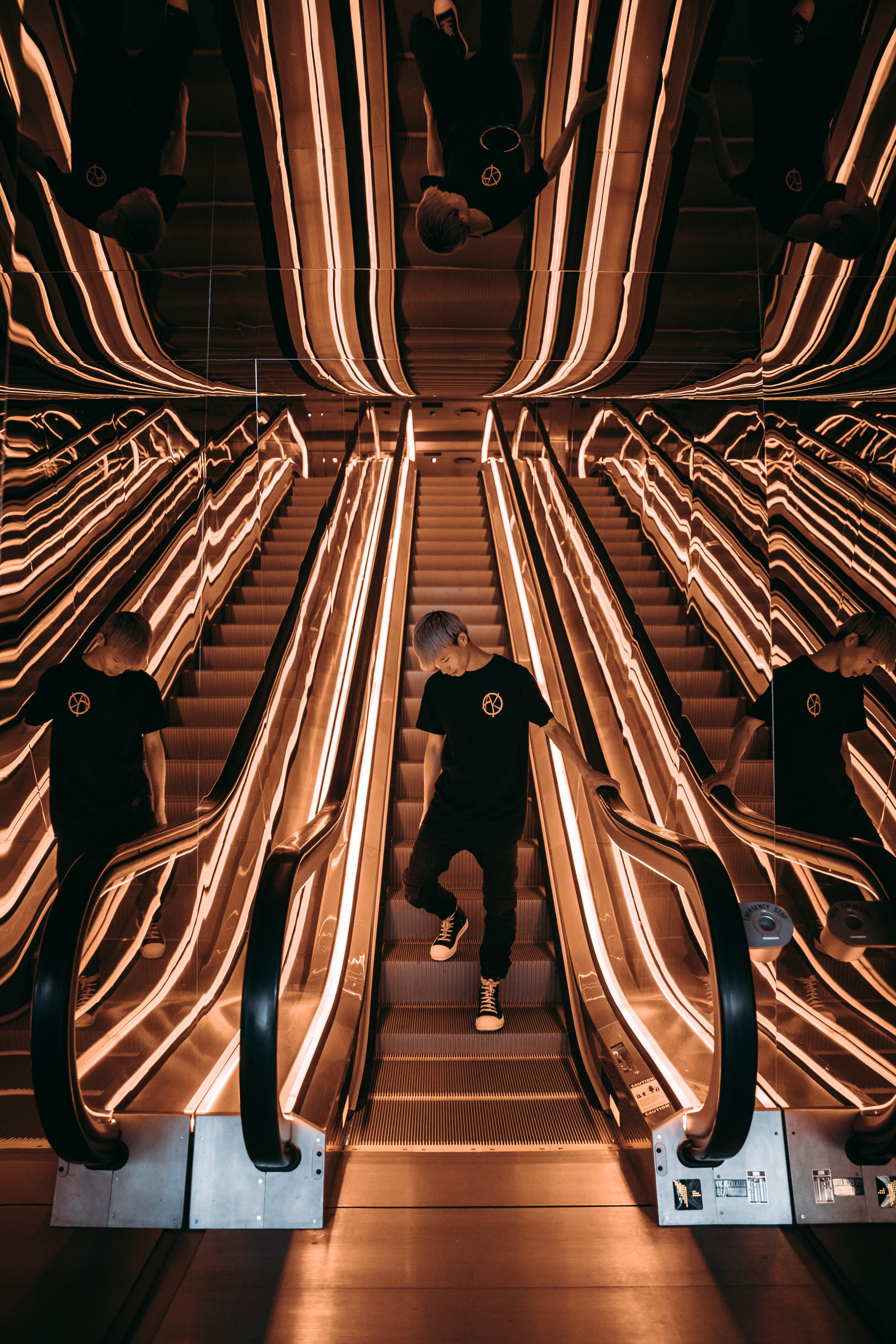 A man wearing all black reflects in two mirrors, as he rides an escalator while looking down.