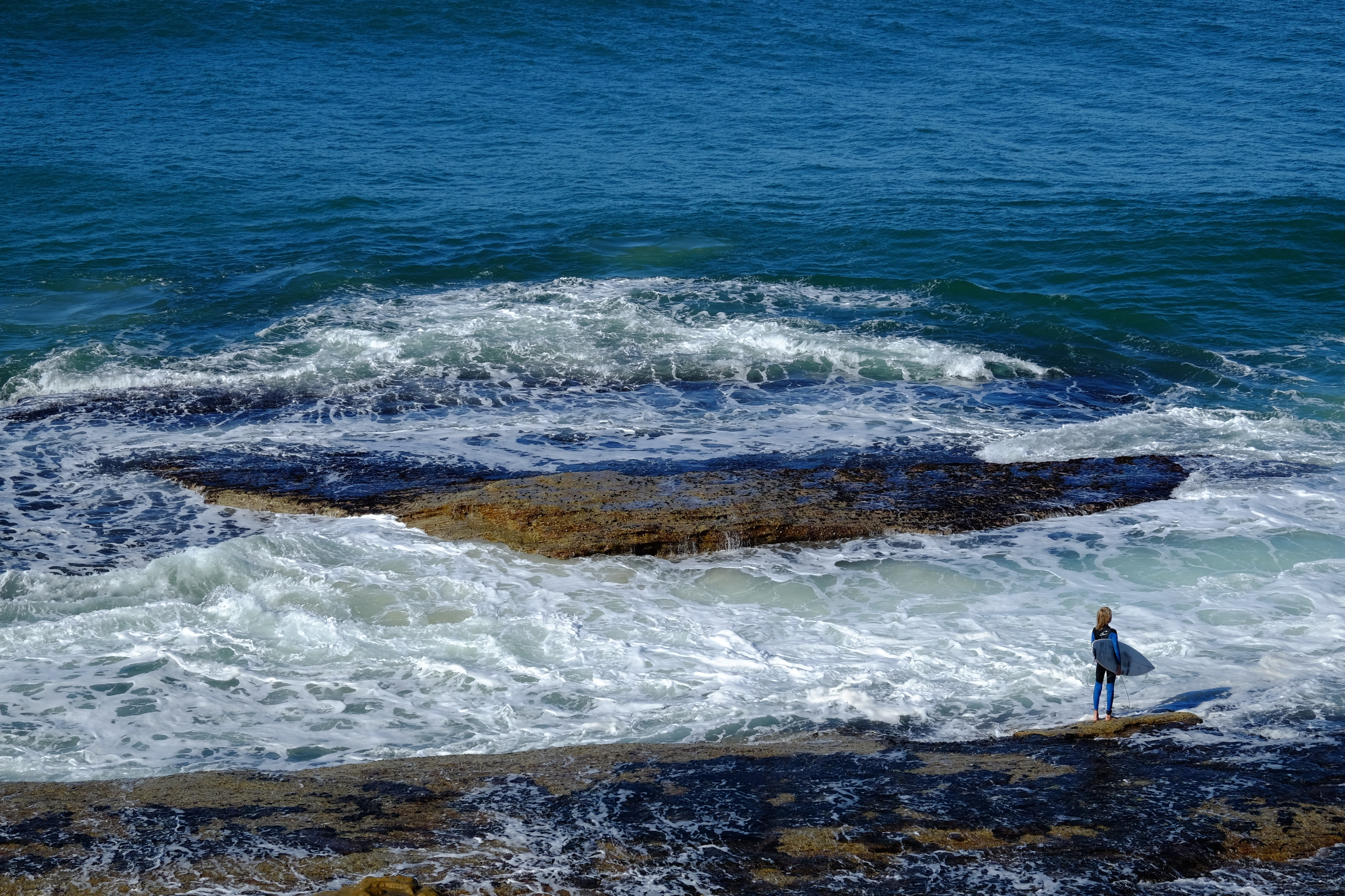 Surfer standing on the rock that is washed up by the ocean at Bondi Beach