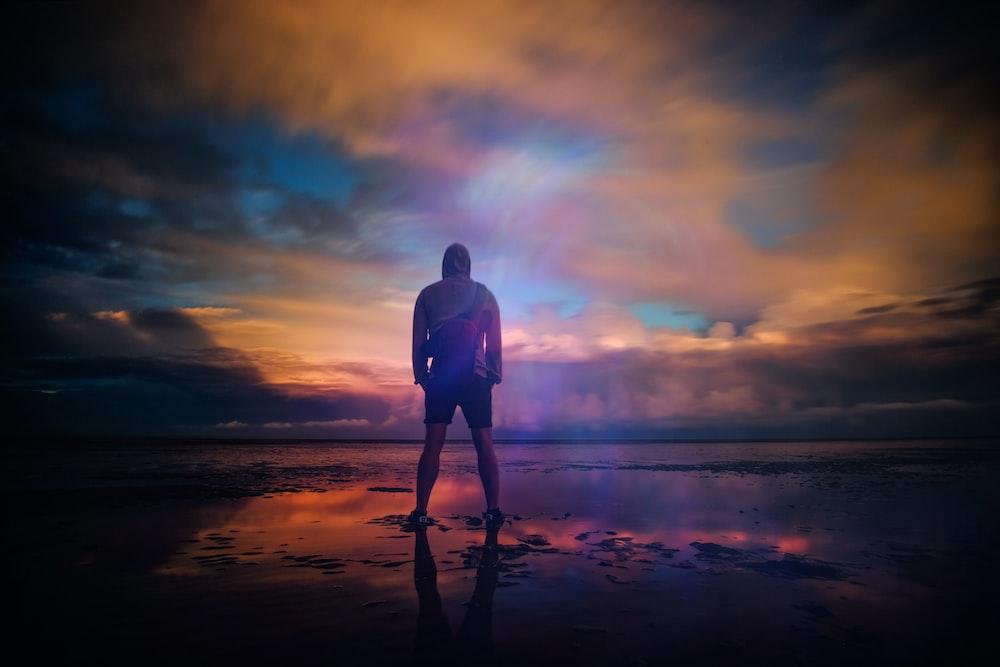水を見ながらニューロムニーのビーチで意気揚々と立っている男性