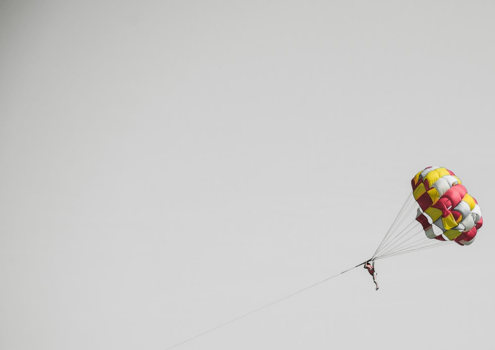 person riding on a parasailing during daytime