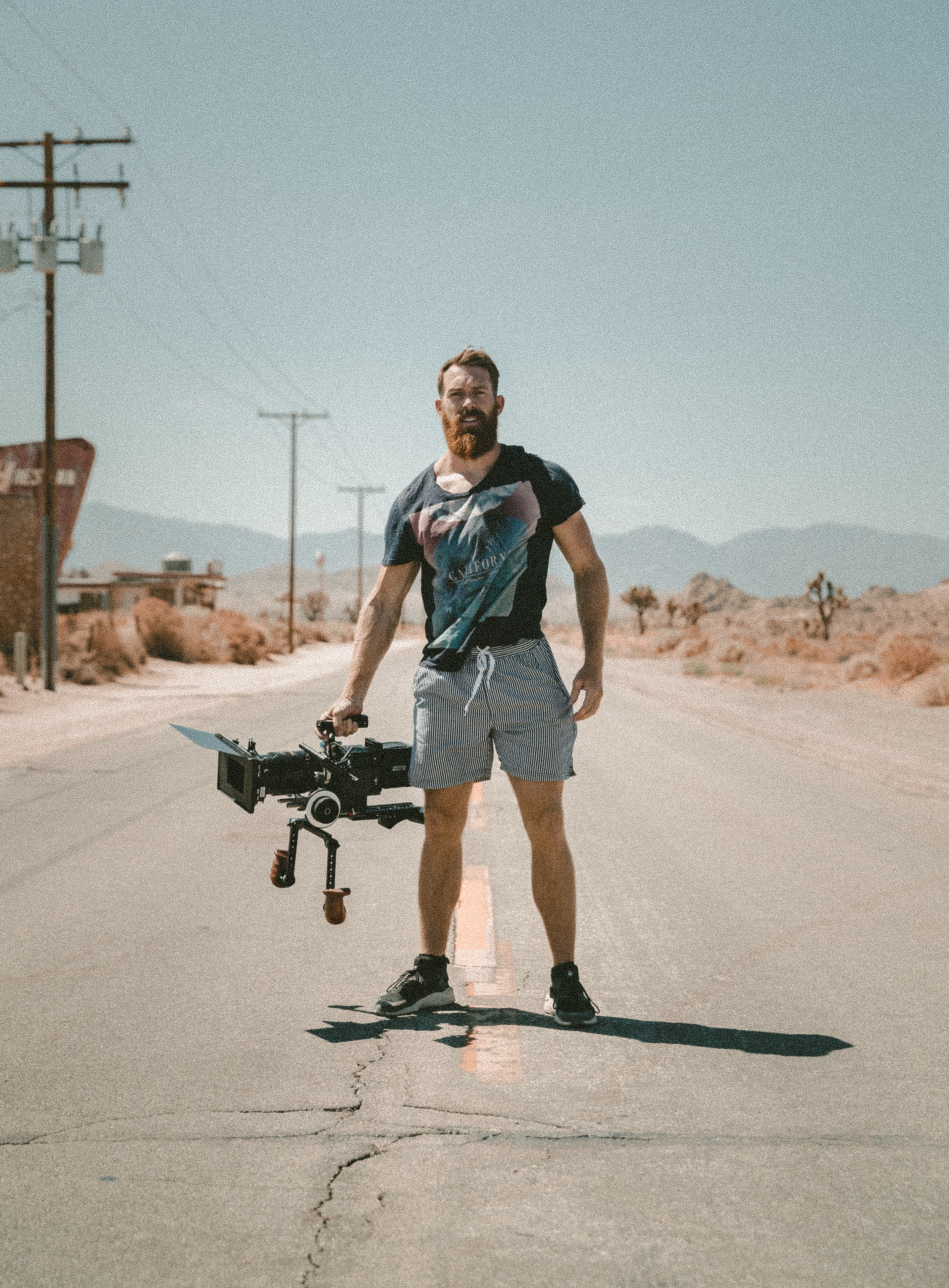 Portrait of a filmmaker with a camera in the middle of a desert road