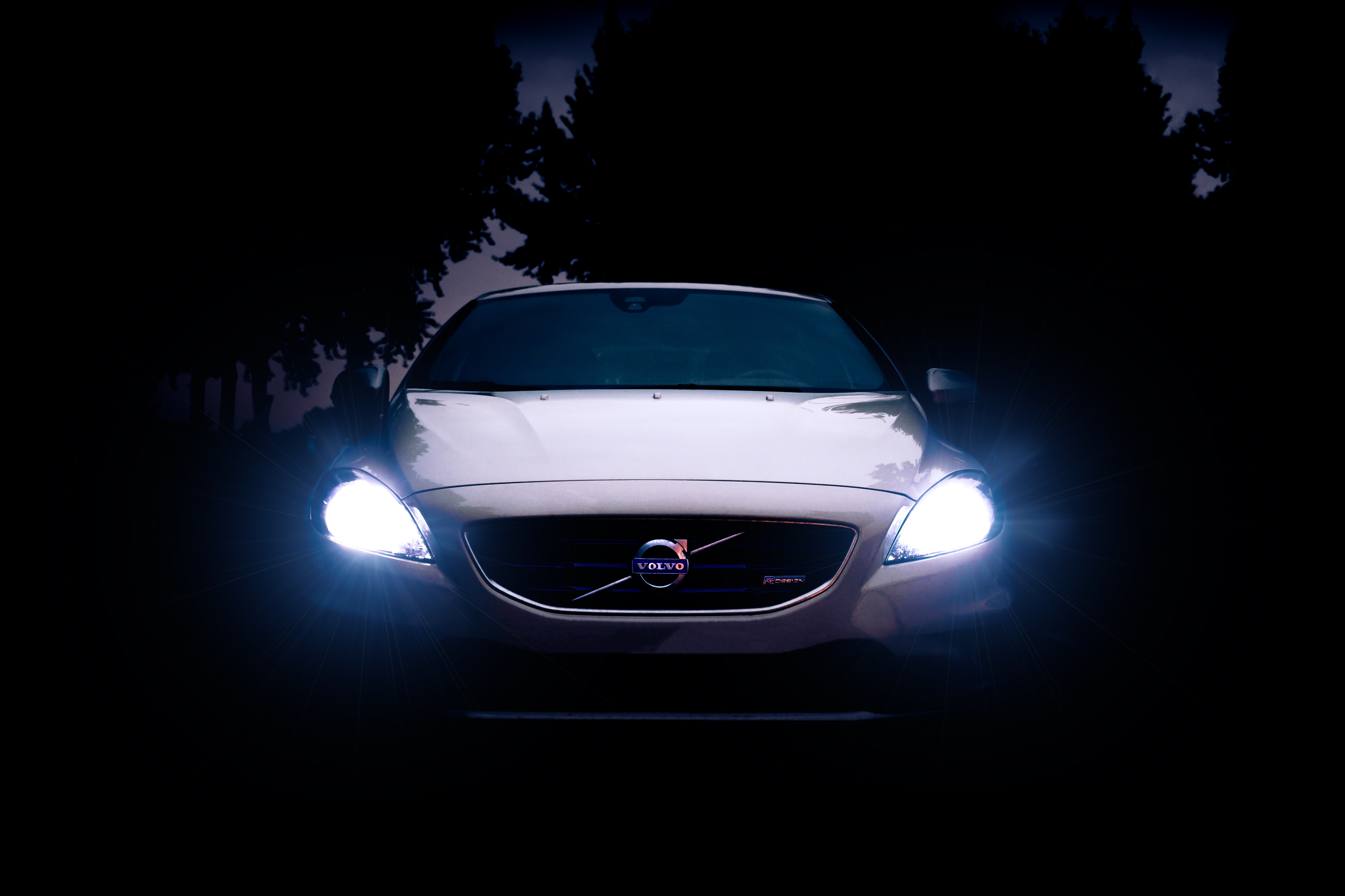 silver Volvo car with headlights on during night